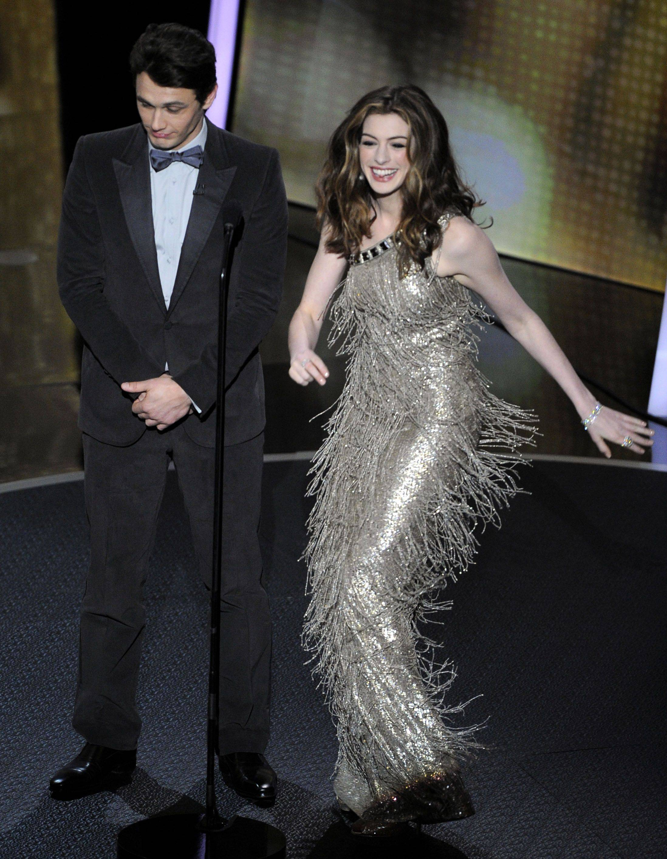 Associated PressAnne Hathaway, with her co-host James Franco, shows off one of her many gowns during the ceremony.
