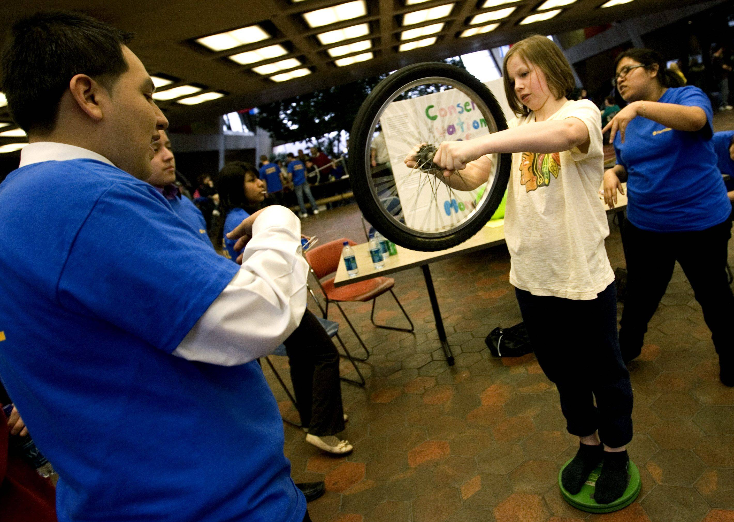 "Richard Komendanchik, 13, of Downers Grove tries out a display called ""Conservation Of Angular Momentum"" with help from students Gabriel Cerda, left, and Elaine Ocampo of Cristo Rey Jesuit High School in Chicago."