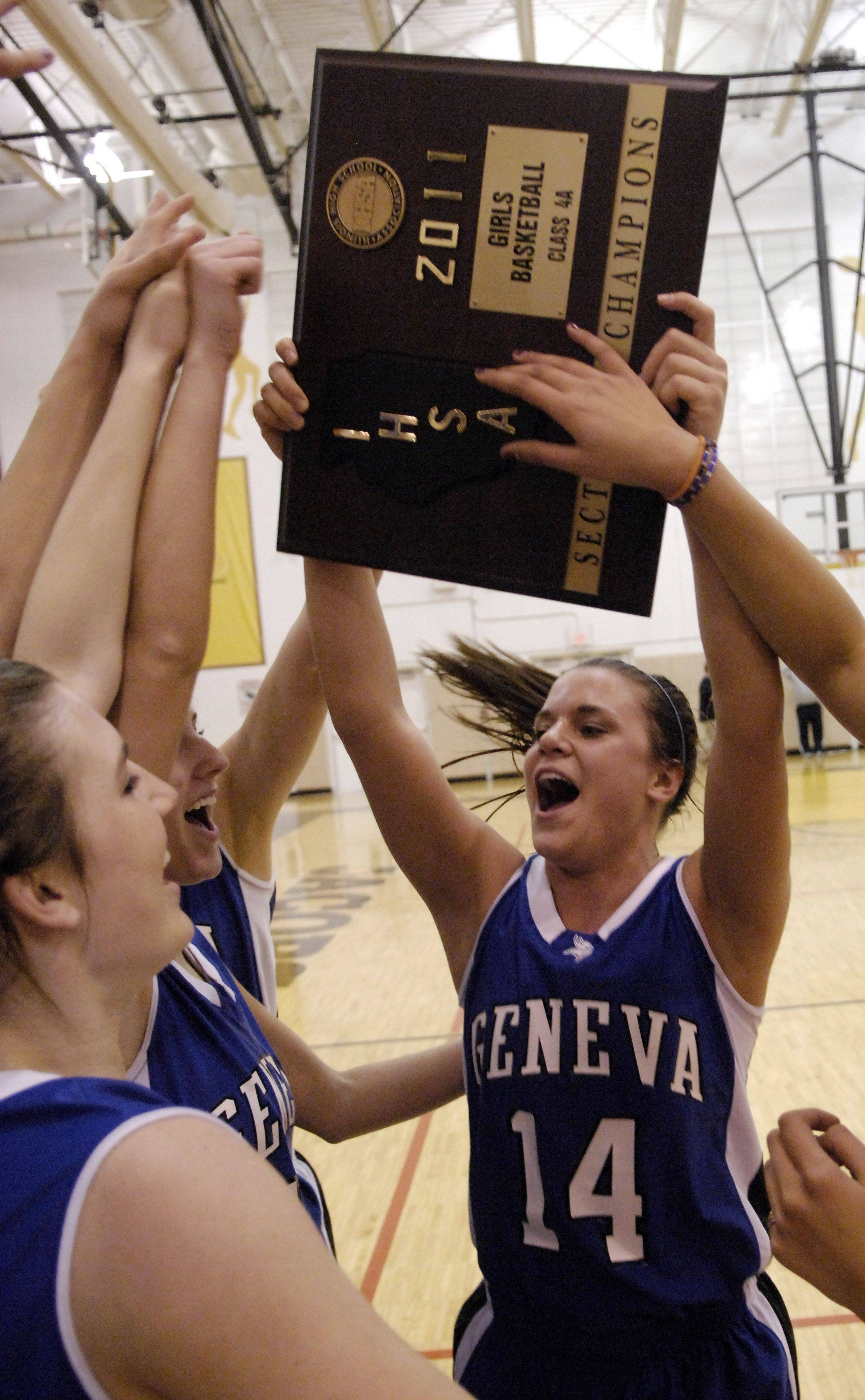 Geneva's Kat Yelle hoists up the sectional championship plaque following their win over Cary-Grove Thursday at Jacobs High School in Algonquin.