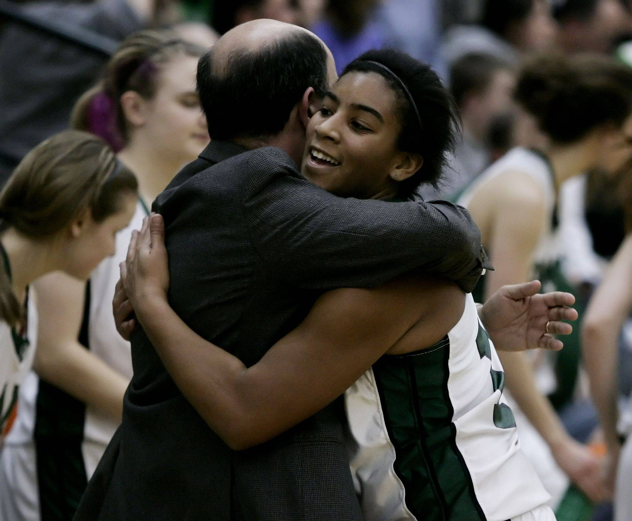 Grayslake Central guard Alex Scarbro is hugged by coach Steve Ikenn at the Class 3A girls high school sectional basketball championship Thursday against Johnsburg. Grayslake Central won the game 69-46.