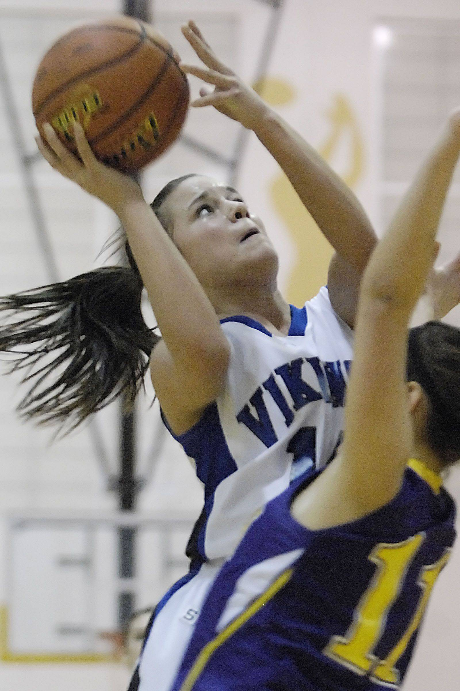 Geneva's Kat Yelle scores over Hononegah's Meg Macy Tuesday in the sectional semifinal game in Algonquin.