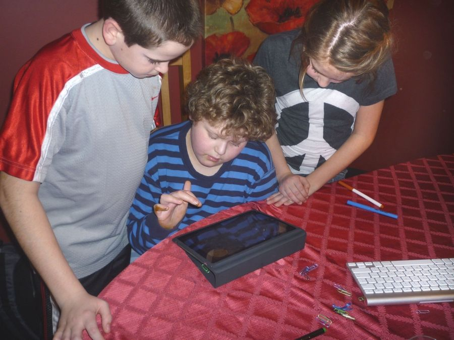 John Reisel, 12, center, uses an iPad at South Middle School in Arlington Heights to help him cope with autism symptoms.