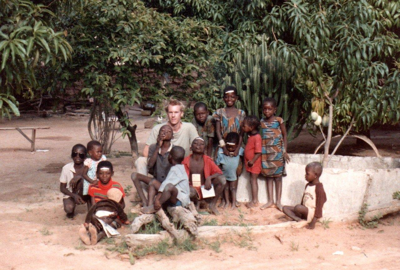 "Rich Johnson, sometime between 1984 and 1986, in the West African courtyard where he stayed. ""I lived with a family that had two wives and five kids between them,"" he related."