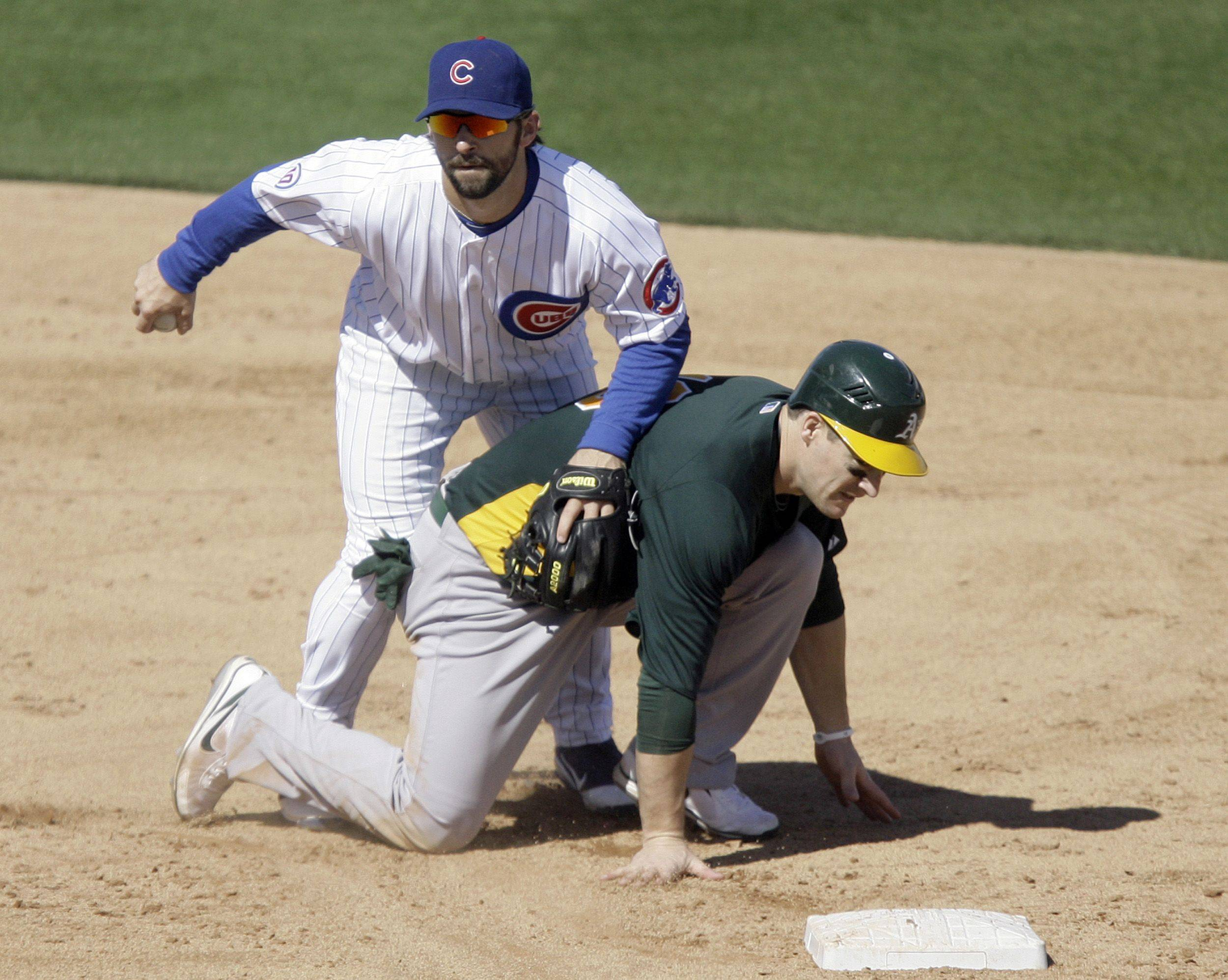 Chicago Cubs second baseman Blake DeWitt, left, is forced to hang onto the ball as Oakland Athletics' Josh Willingham, right, slides to break up the double play during the third inning of a spring training baseball game Sunday, Feb. 27, 2011, at HoHoKam Park in Mesa, Ariz.