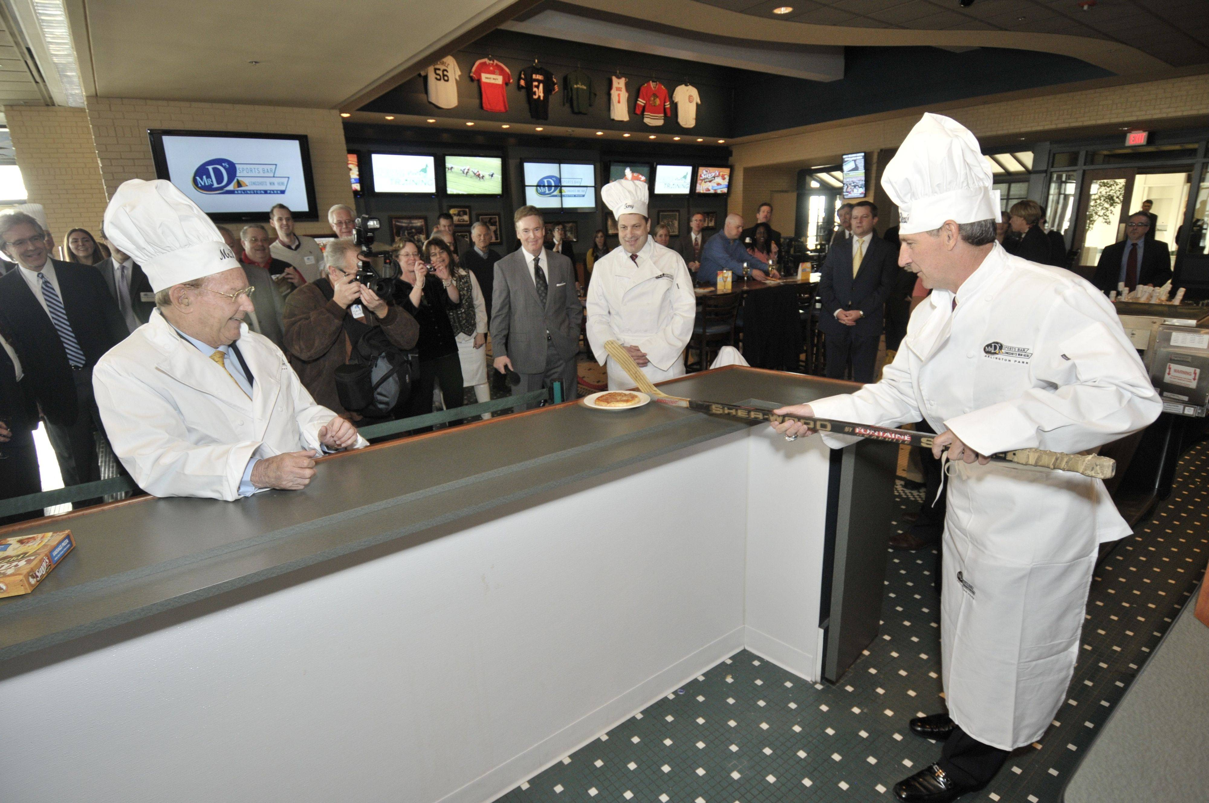 "Chicago Blackhawks legend Denis Savard, right, delivers a ""Savy's Pizza"" to Arlington Park Chairman Dick Duchossois at Friday's grand reopening of Mr. D's Sports Bar at the horse racing track."