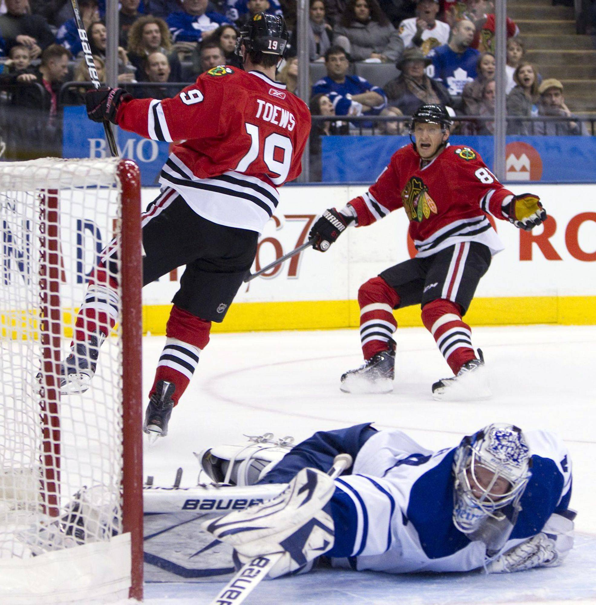 The Blackhawks' Jonathan Toews celebrates his first-period goal with teammate Marian Hossa in front of Toronto Maple Leafs goaltender James Reimer. The Hawks extended their winning streak to eight games.