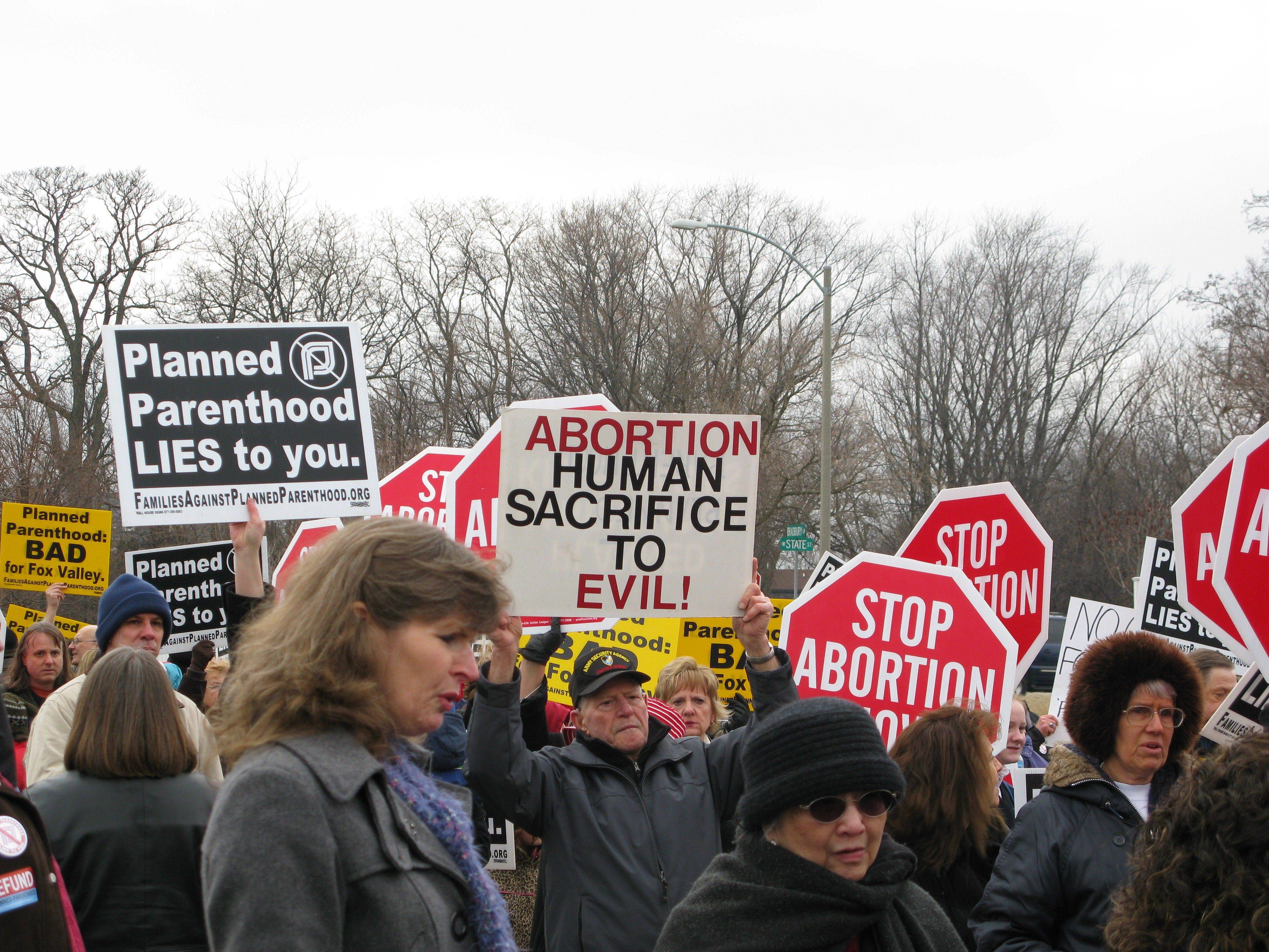 Abortion opponents attempted to chant down abortion rights advocates Monday outside Congressman Randy Hultgren's office. The two sides hosted competing rallies as they each view the pending cut of federal funds for Planned Parenthood as a major social and moral battle for the current Congress.