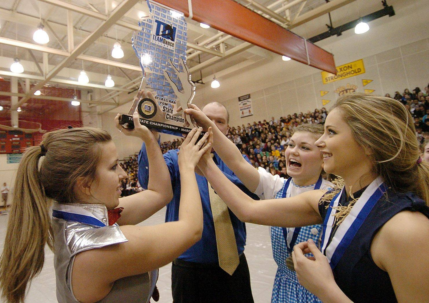 From left, Lauren Berndt, Marisa Grzeszkowiak and Rachel Desimone hoist their 1st place State Poms trophy with Schaumburg High School Principal Tim Little.