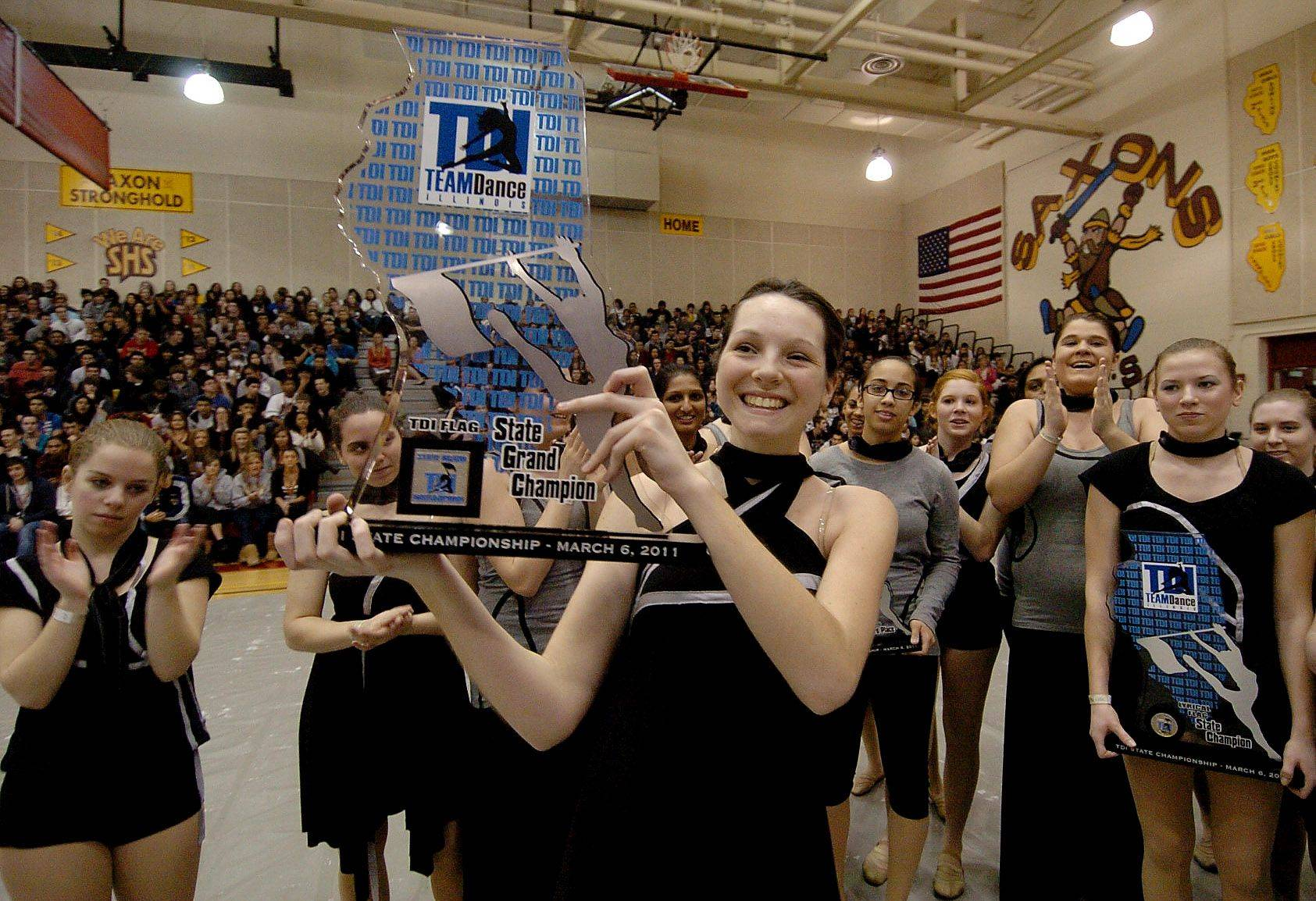 Jill Tegtmeyer hoists the state Grand Champion trophy won by the Schaumburg High School Lyrical Flag team.