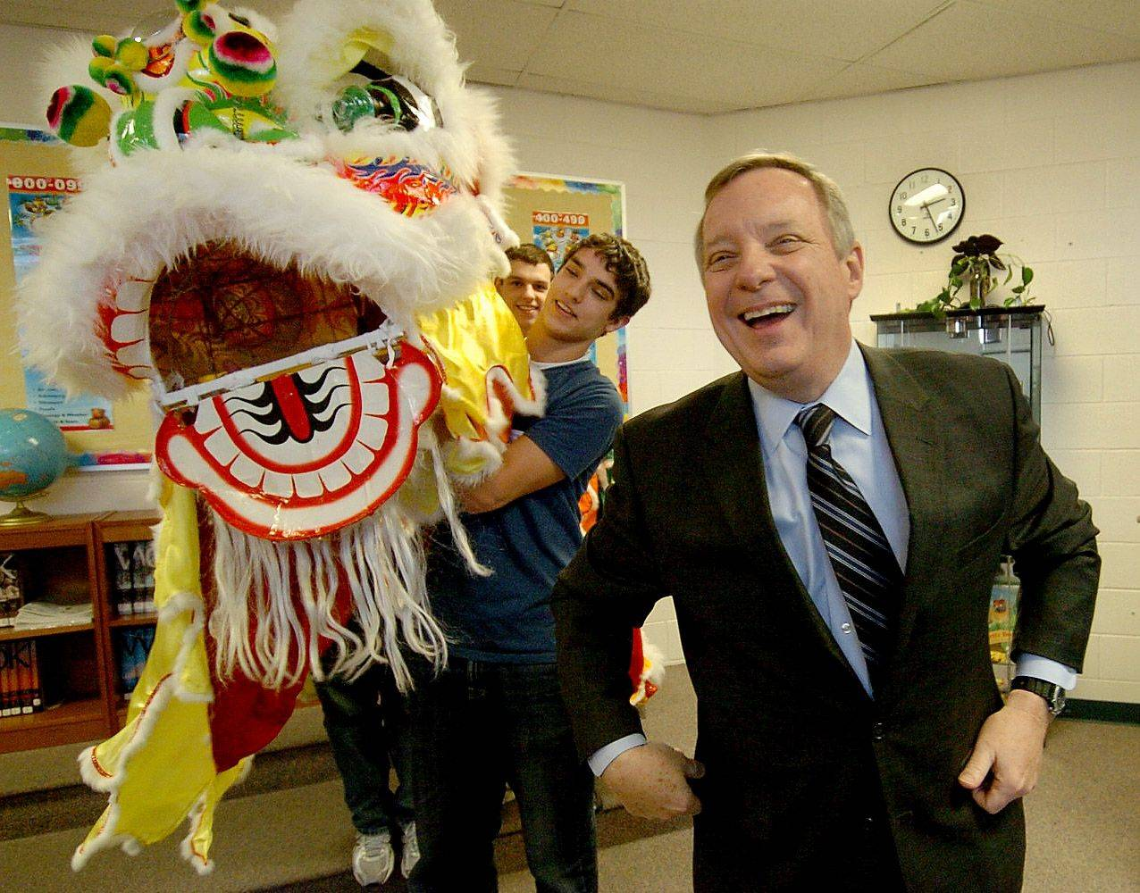 Senator Dick Durbin is shown a traditional Chinese lions head by Barrington High School Chinese class student Connor MacCartney, during Durbin's visit to Barbara Rose School in South Barrington.