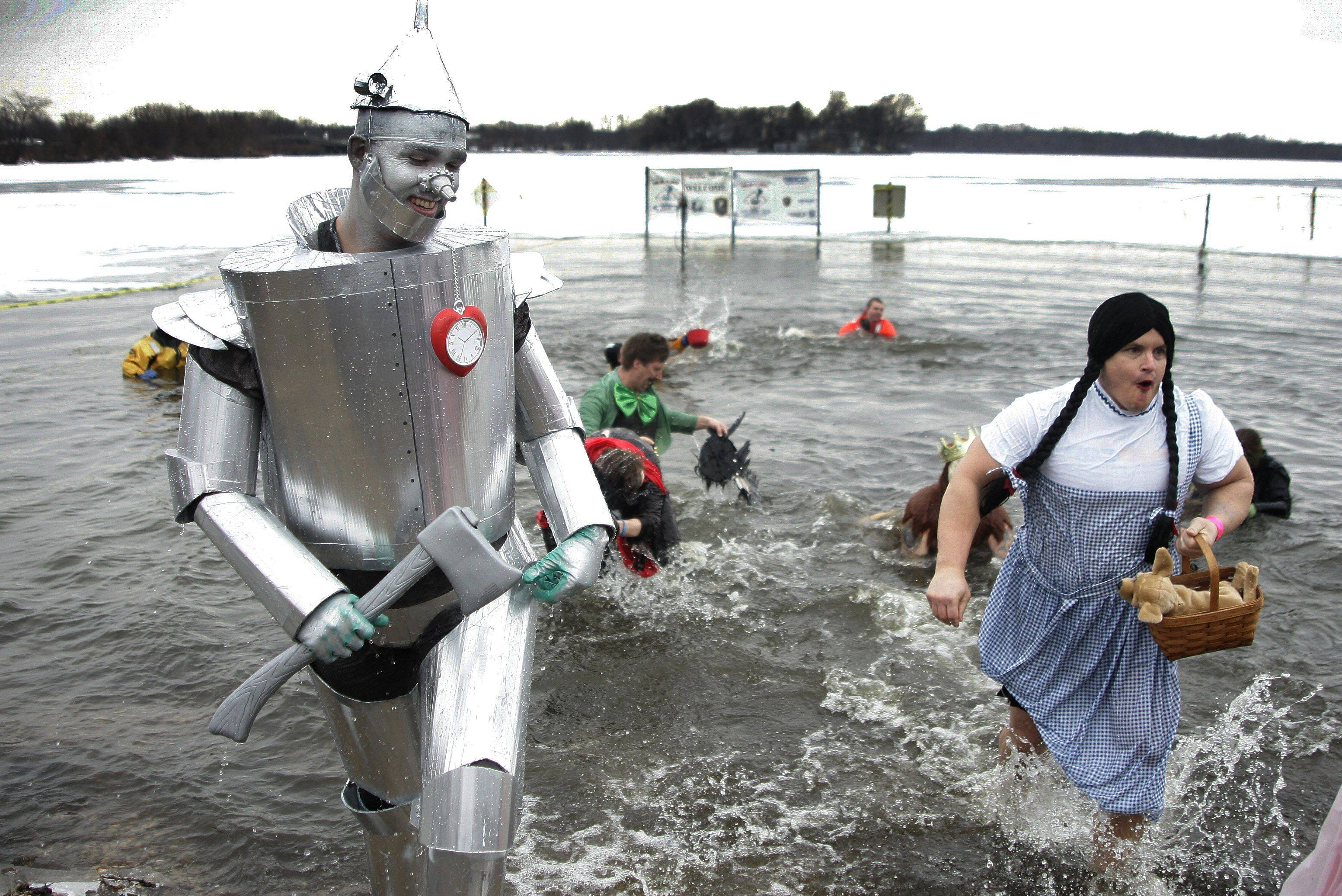"Joe Holtz as the Tin Man and Chuck Foy as Dorothy come out of the water at Lake Front Park during the Fox Lake Polar Plunge Sunday to benefit Special olympics Illinois Northeastern/Area 13. The two are police officers with the Grayslake Police Department and the whole group dressed as characters from ""The Wizard of Oz""."