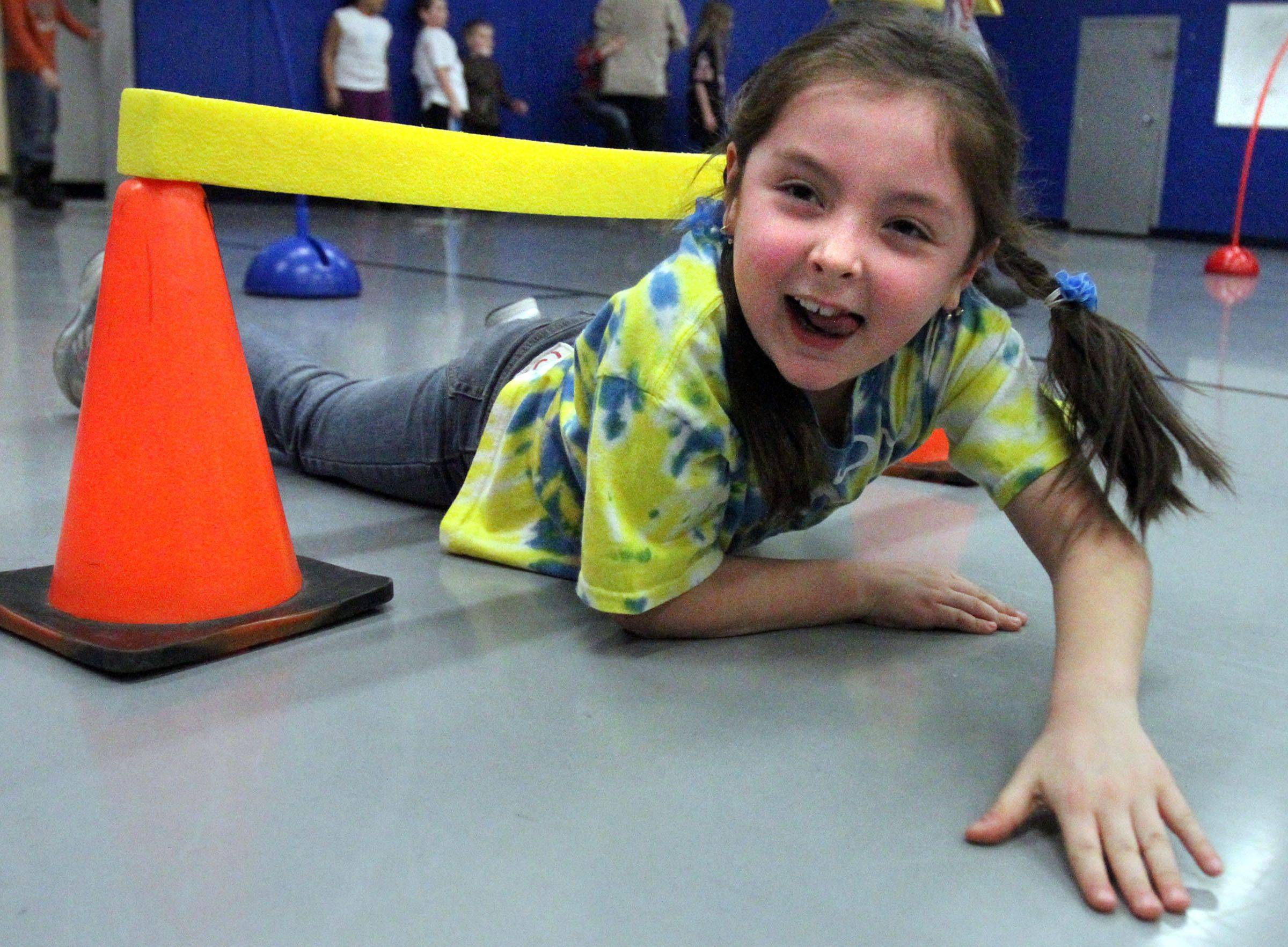 First grader Nathalia Johnson enjoys the exercise course as she slides under a foam bar on cones at Grayslake District 46 wellness night at Avon School in Round Lake Beach on Friday.