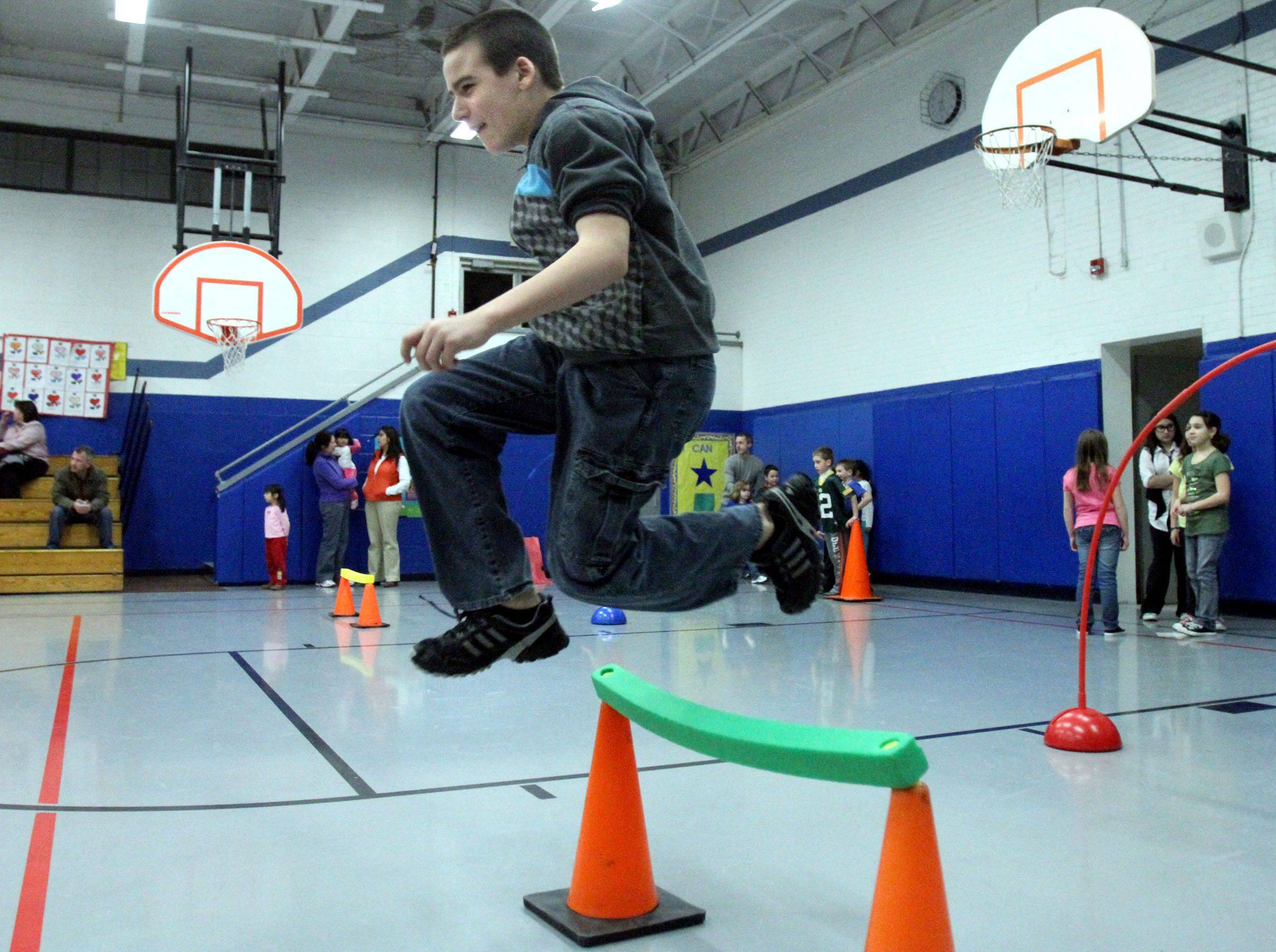 Michael Jones, 11, leaps over a foam bar on cones within an exercise course in the gym at Avon School during Grayslake District 46 wellness night.
