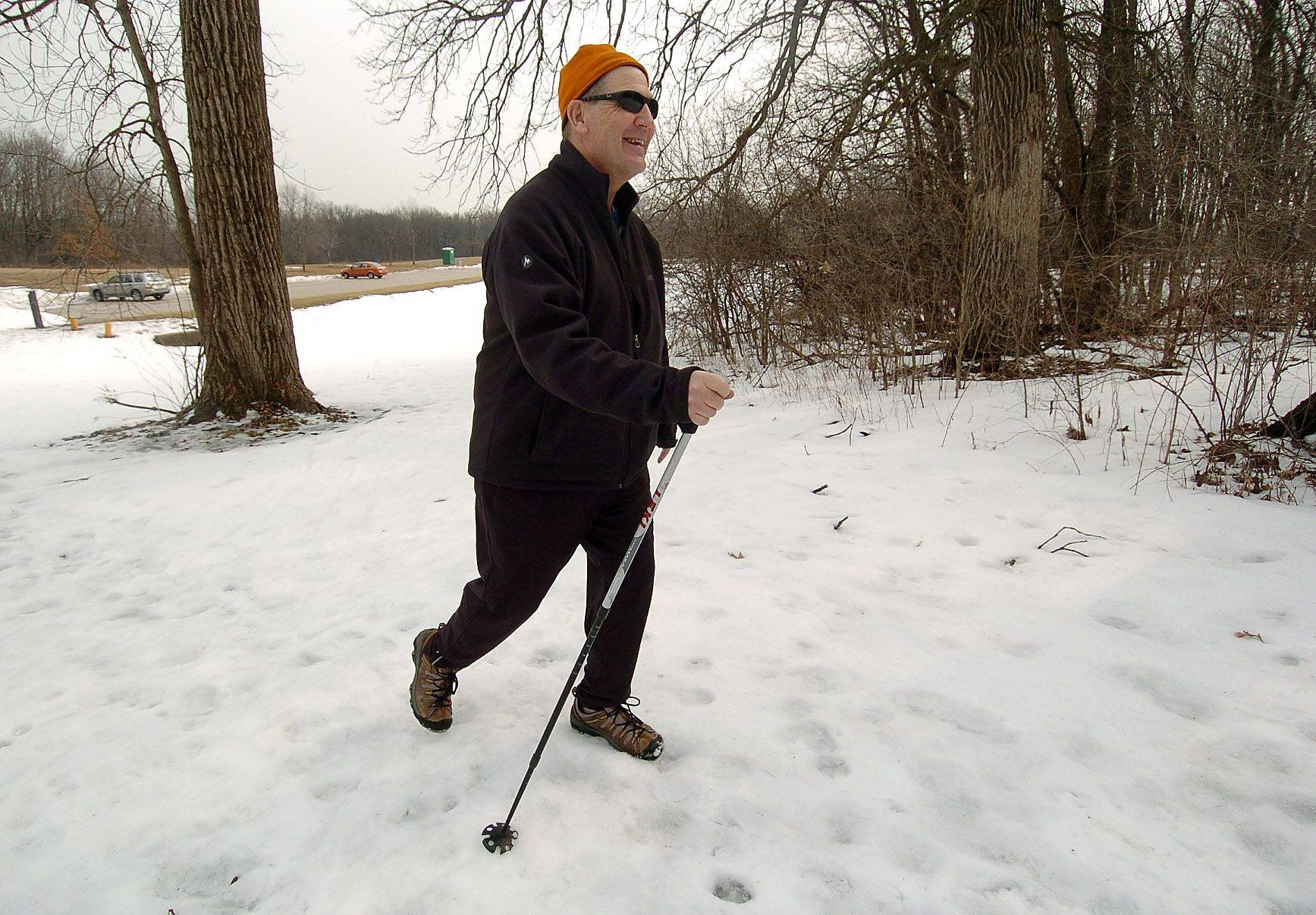 Bill Baltutis of Palatine usually cross country skis a couple of times a week when the conditions are right. Here he uses his ski pole to navigate through a thawing Deer Grove West Forest Preserve in Palatine.