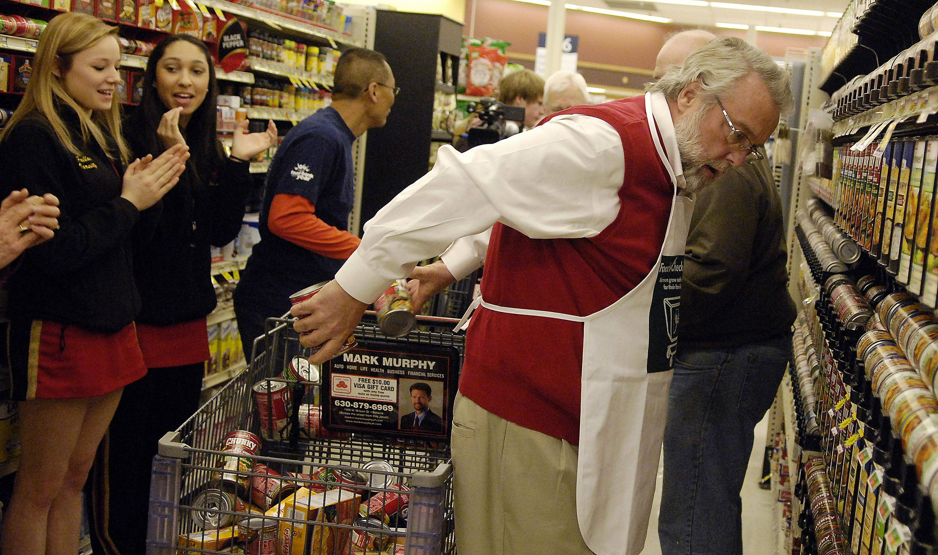 Mayor Tom Weisner of Aurora uses his own special method to fill his cart as quickly as possible during the 10th-annual Farm Bureau Food Check-Out Challenge Jewel in Batavia Friday. He collected $1001.05 in food for the Aurora Interfaith Food Pantry.