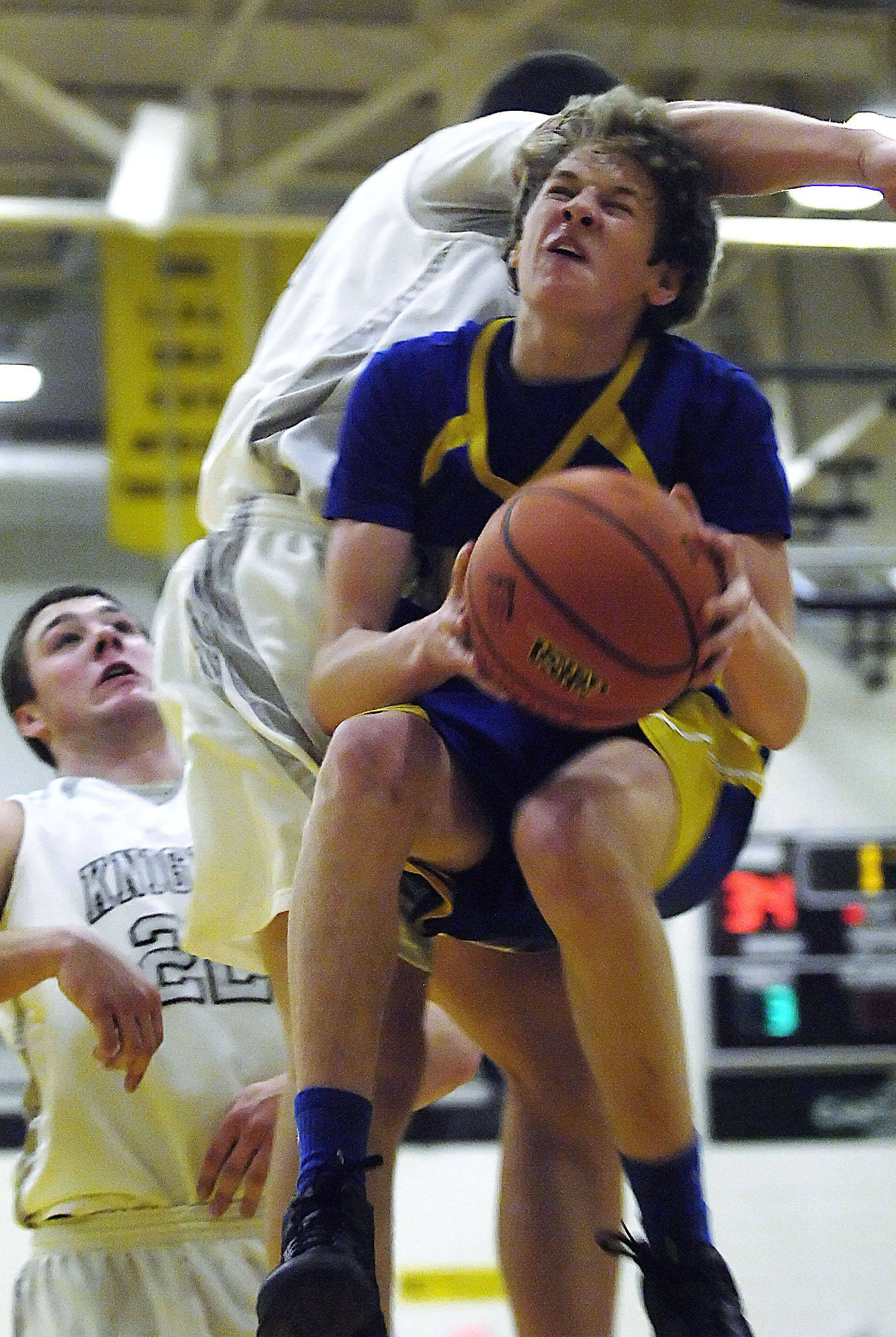 Kaneland's Daniel Helm fouls Aurora Central Catholic's Ryan Harreld as he drives to the basket Wednesday in Sycamore.