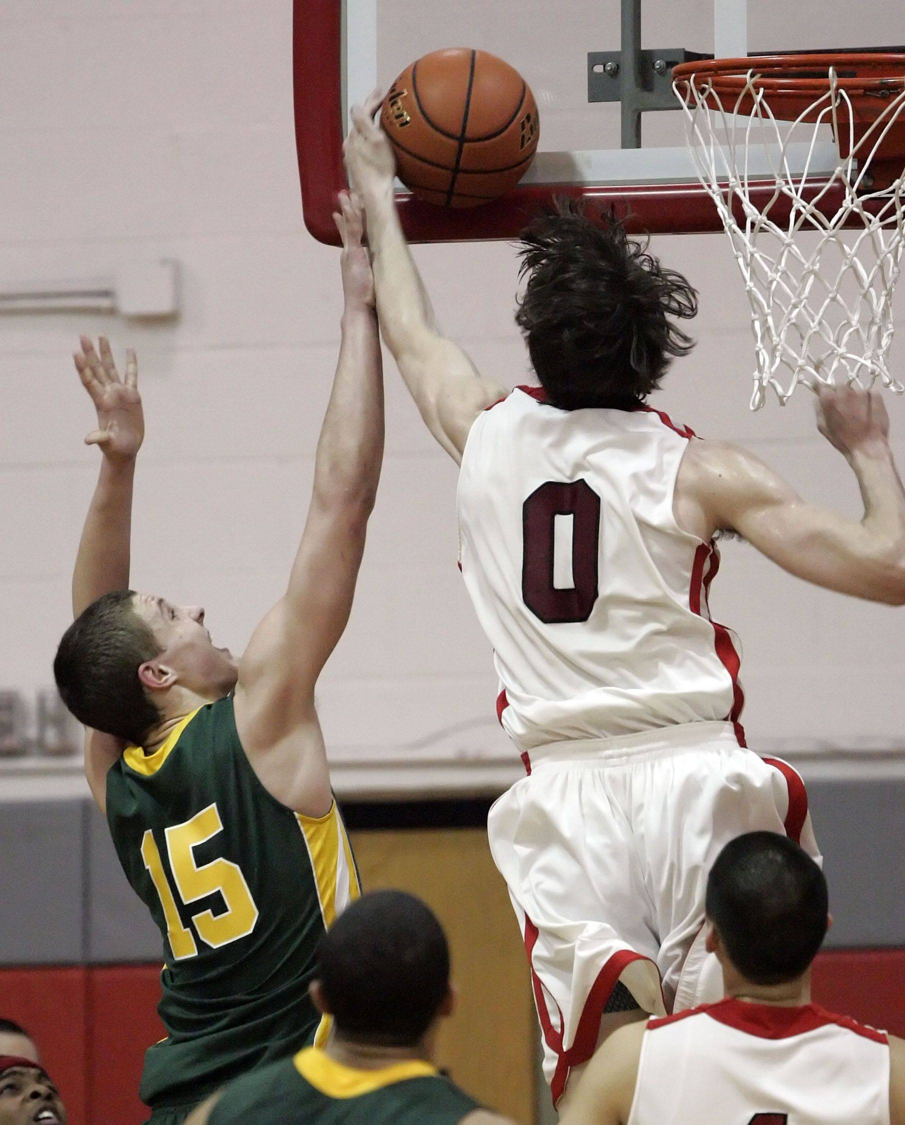 Mundelein's Ryan Sawvell blocks the shot of Stevenson's Troy Radke during their regional semifinal Tuesday night at Mundelein High School.