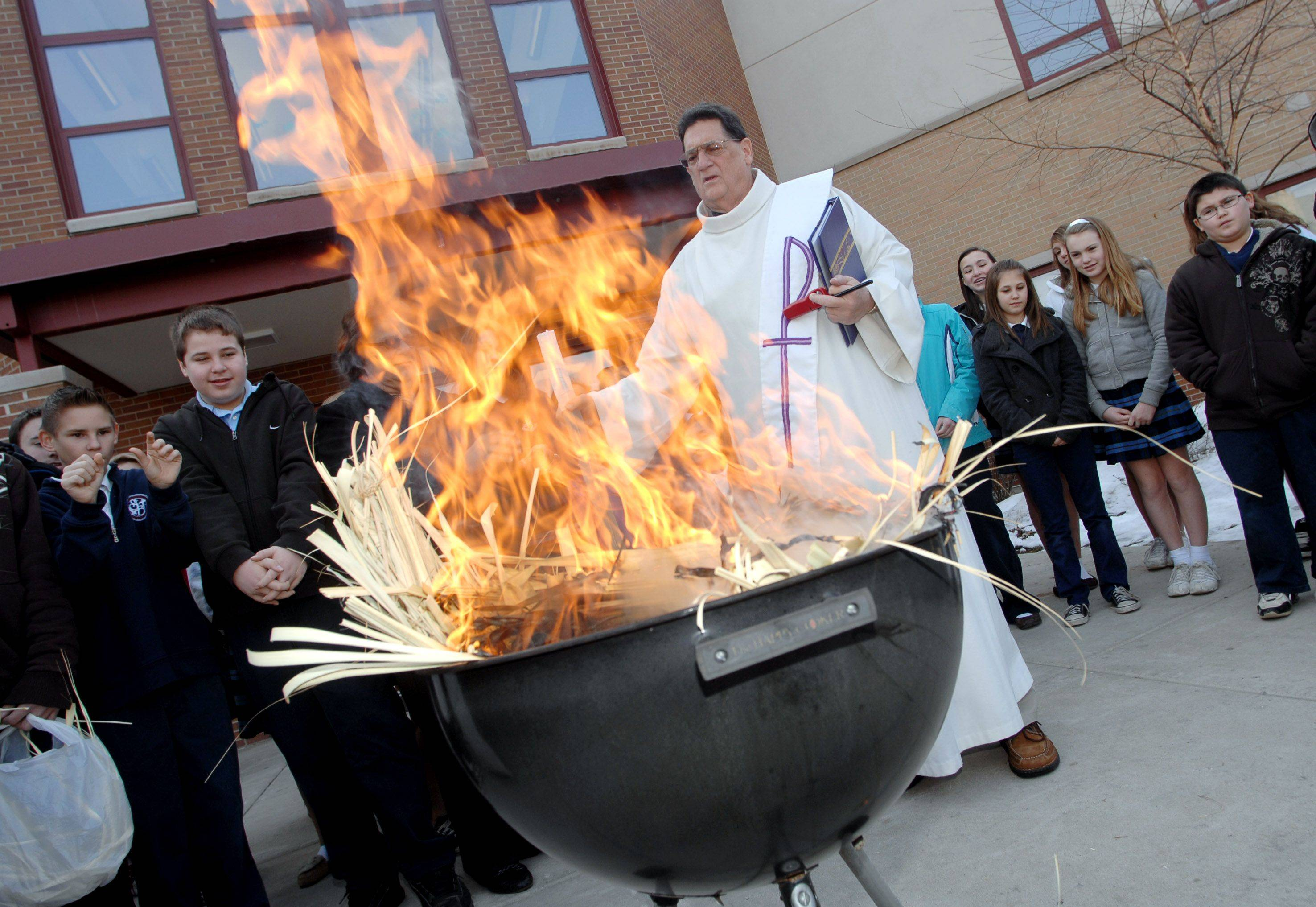 Deacon Larry Spohr conducts the palm burning celebration at St. Bede School in Ingleside Tuesday morning. St. Bede Catholic Church will use the ashes for their four Ash Wednesday services.