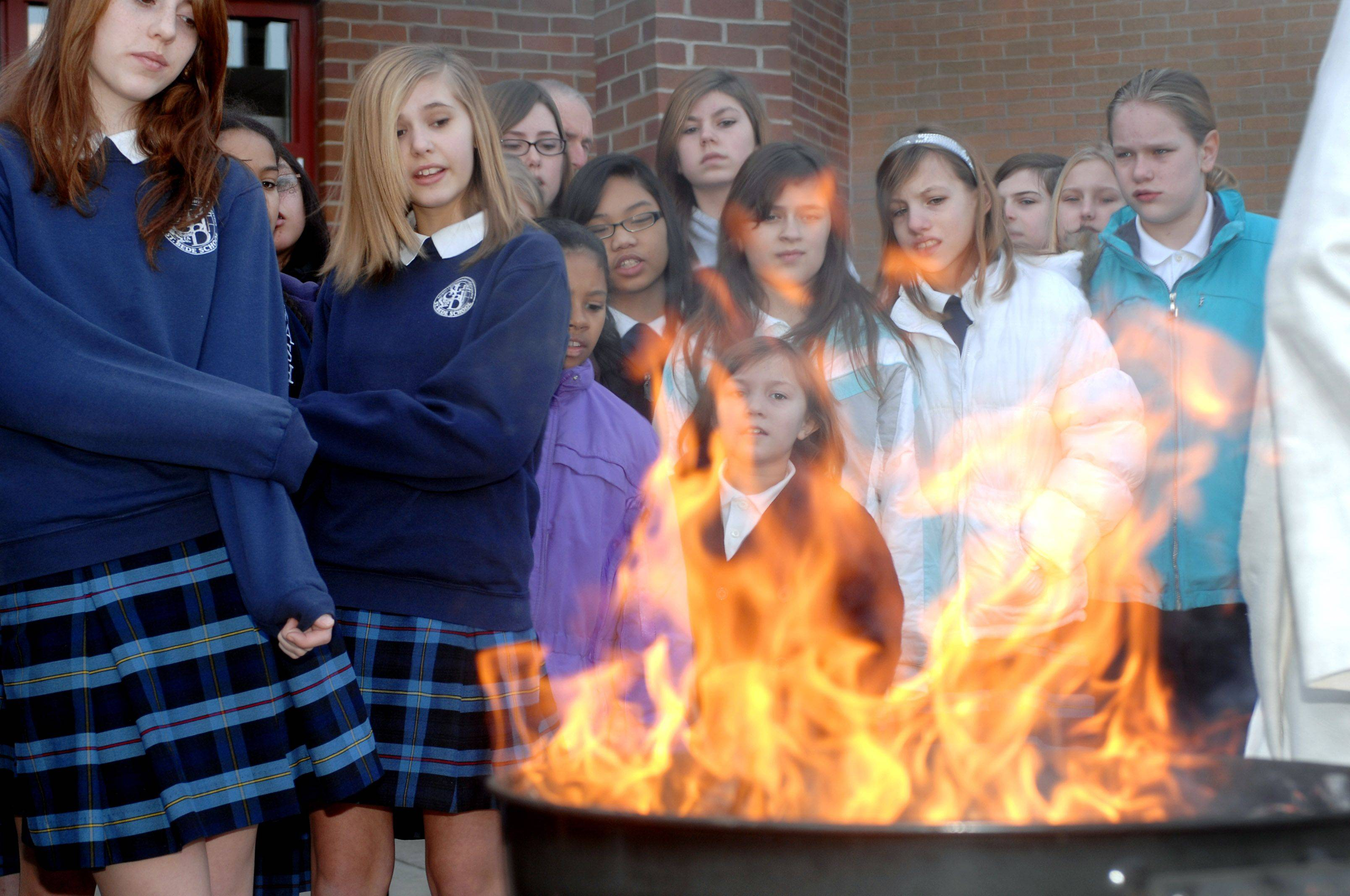 St. Bede School students watch the palm branches burn Tuesday morning in preparation of their church's Ash Wednesday services in Ingleside.