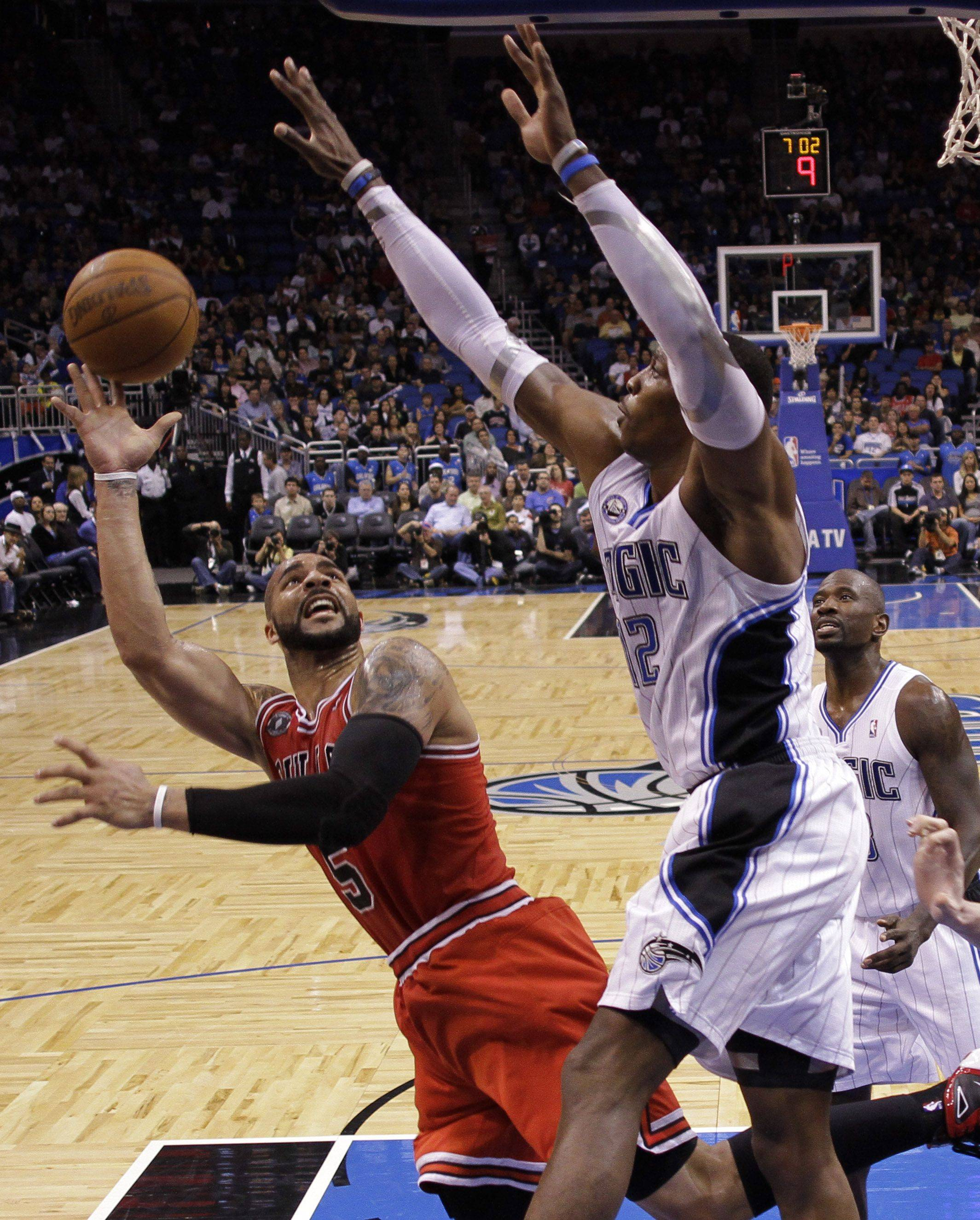 The Bulls' Carlos Boozer puts up a shot over Magic center Dwight Howard during last Friday's victory over Orlando.