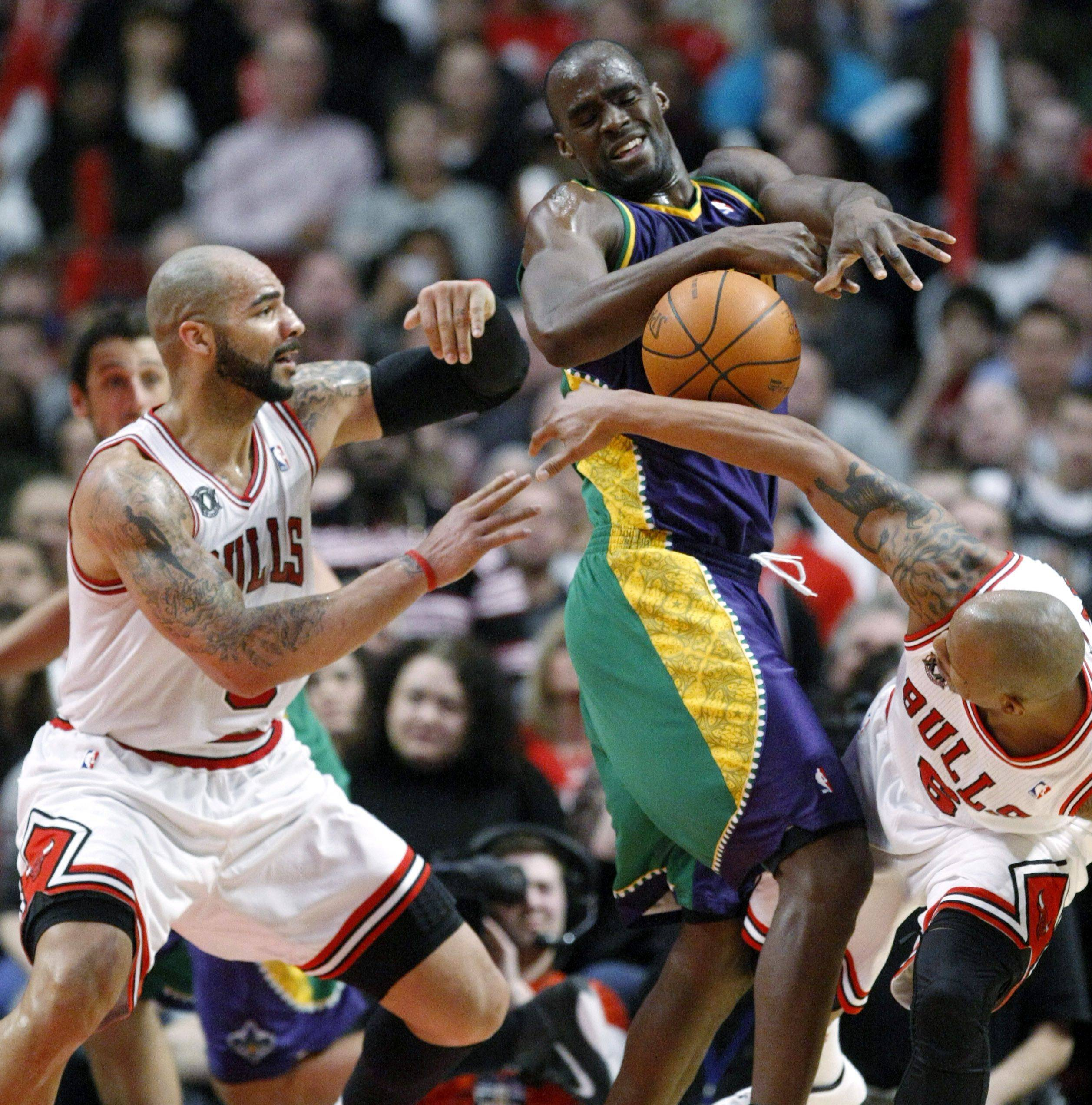 Hornets center Emeka Okafor has the ball stripped away by defensive pressure from Carlos Boozer, left, and Keith Bogans during Monday's Bulls victory.
