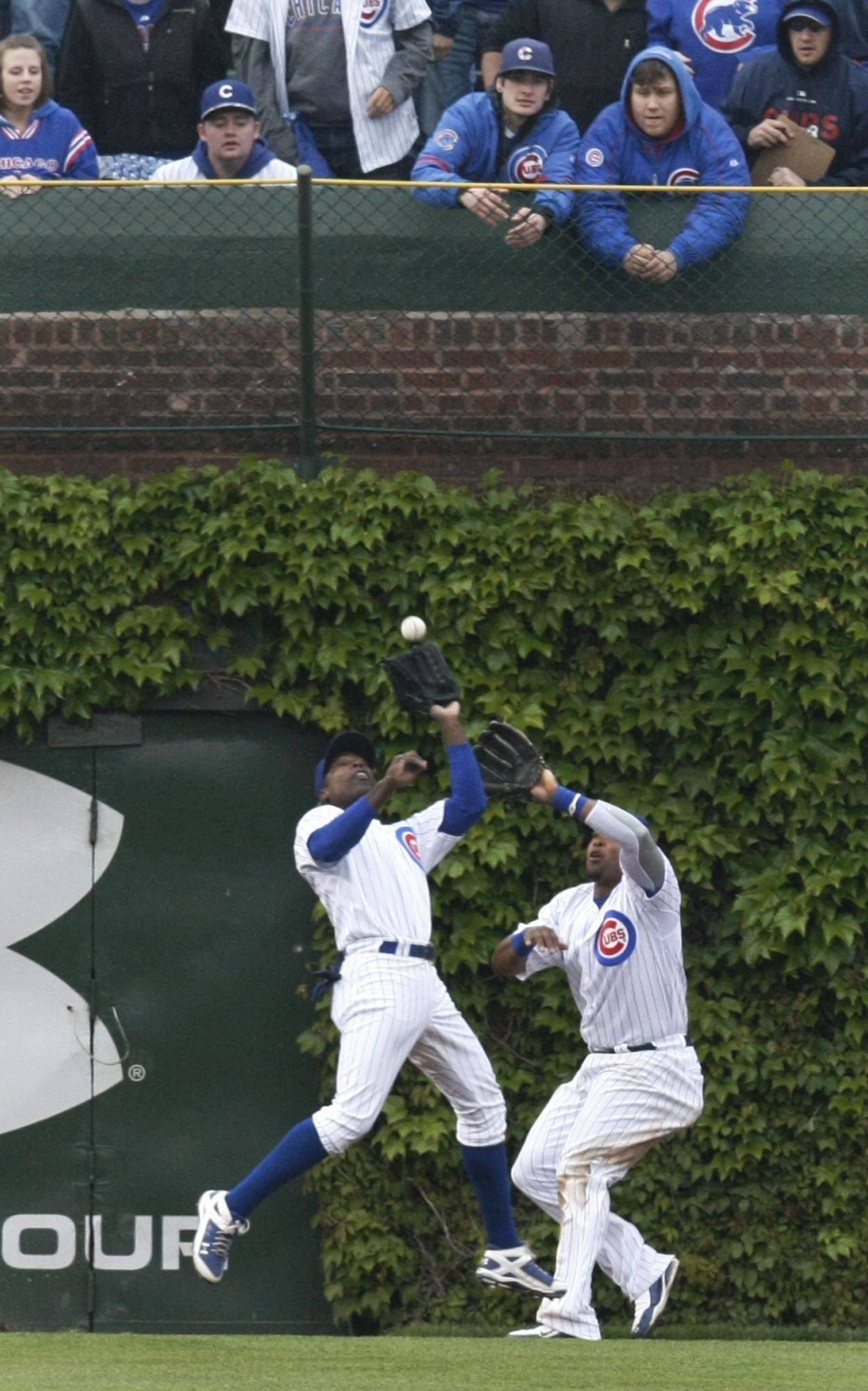 Left fielder Alfonso Soriano, left, leaps in front of center fielder Marlon Byrd to catch a long fly ball last May at Wrigley Field in Chicago.