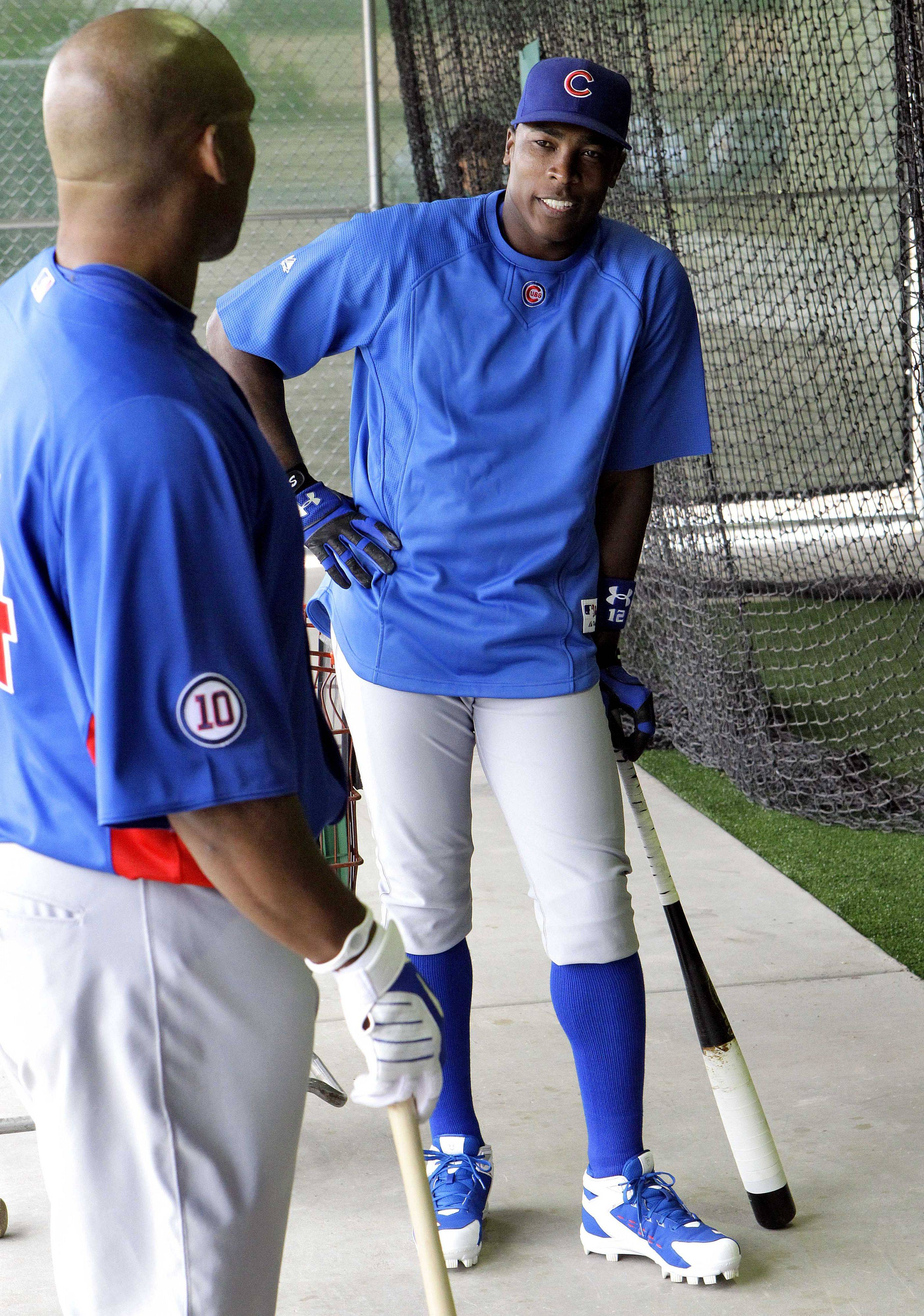Cubs outfielders Alfonso Soriano, right, and Marlon Byrd wait for batting practice to begin at the Cubs' baseball spring training facility in Mesa, Ariz.