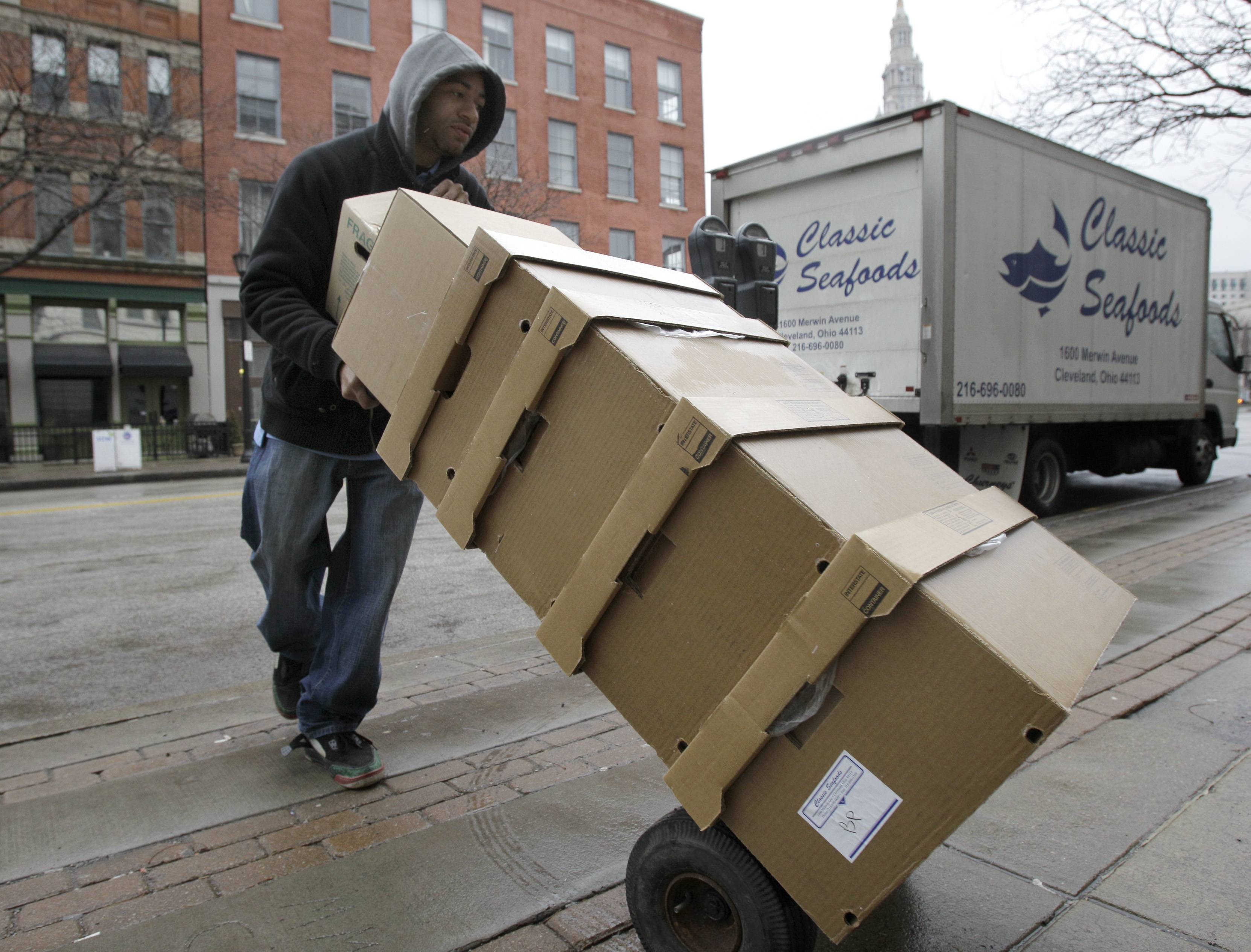 Desmond Wright delivers a dolly load of seafood from wholesaler Classic Seafood to a restaurant in Cleveland on Wednesday.