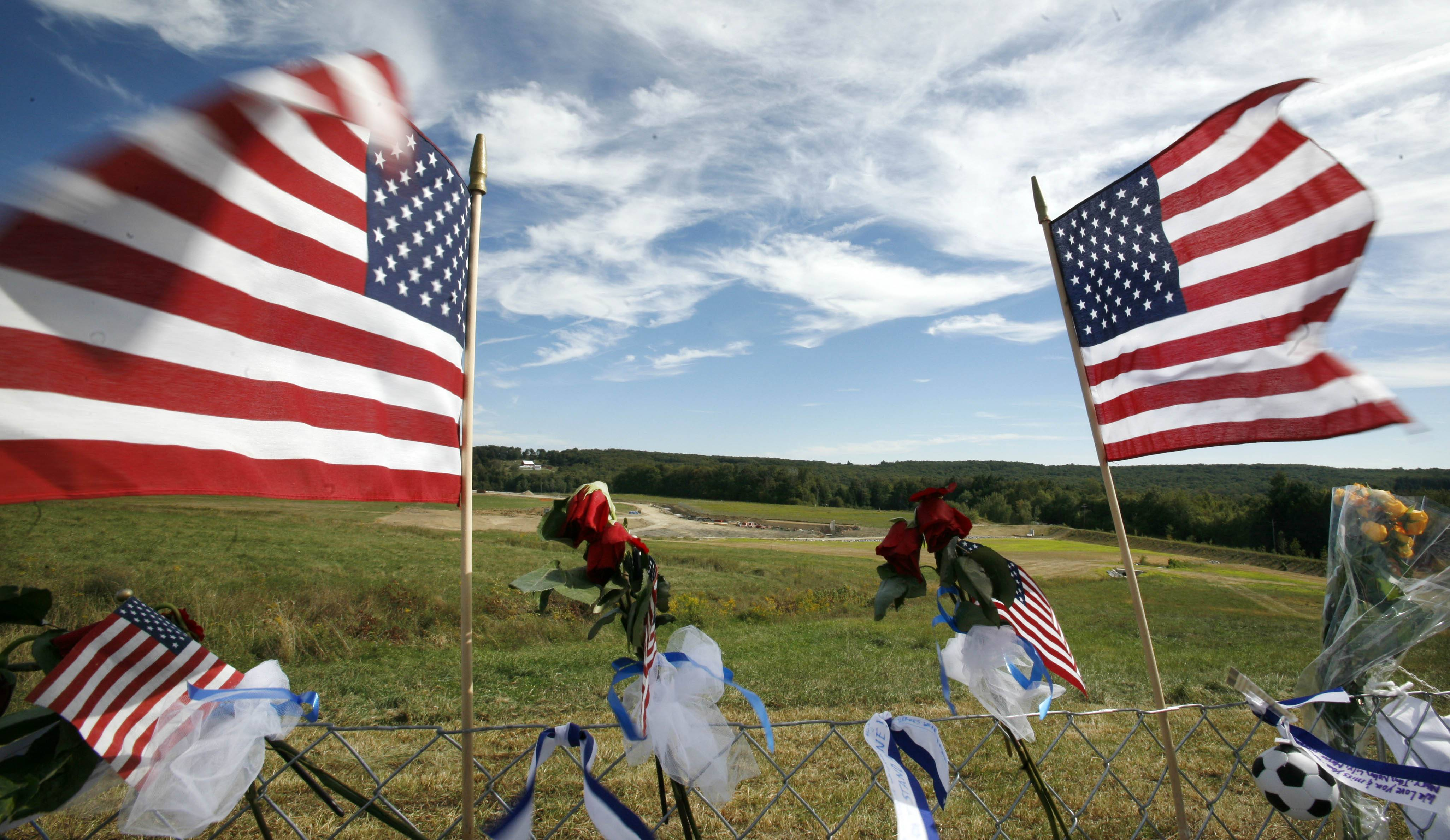 Flags frame the crash site of United Flight 93 at the temporary Flight 93 memorial in Shanksville, Pa.