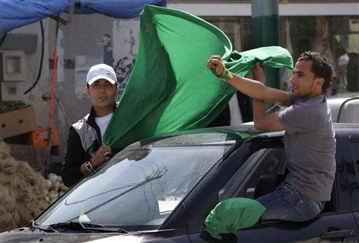 Supporters of Moammar Gadhafi fly the green flag at they drive past foreign journalists in Janzour, 12 miles West of Tripoli. Libya.