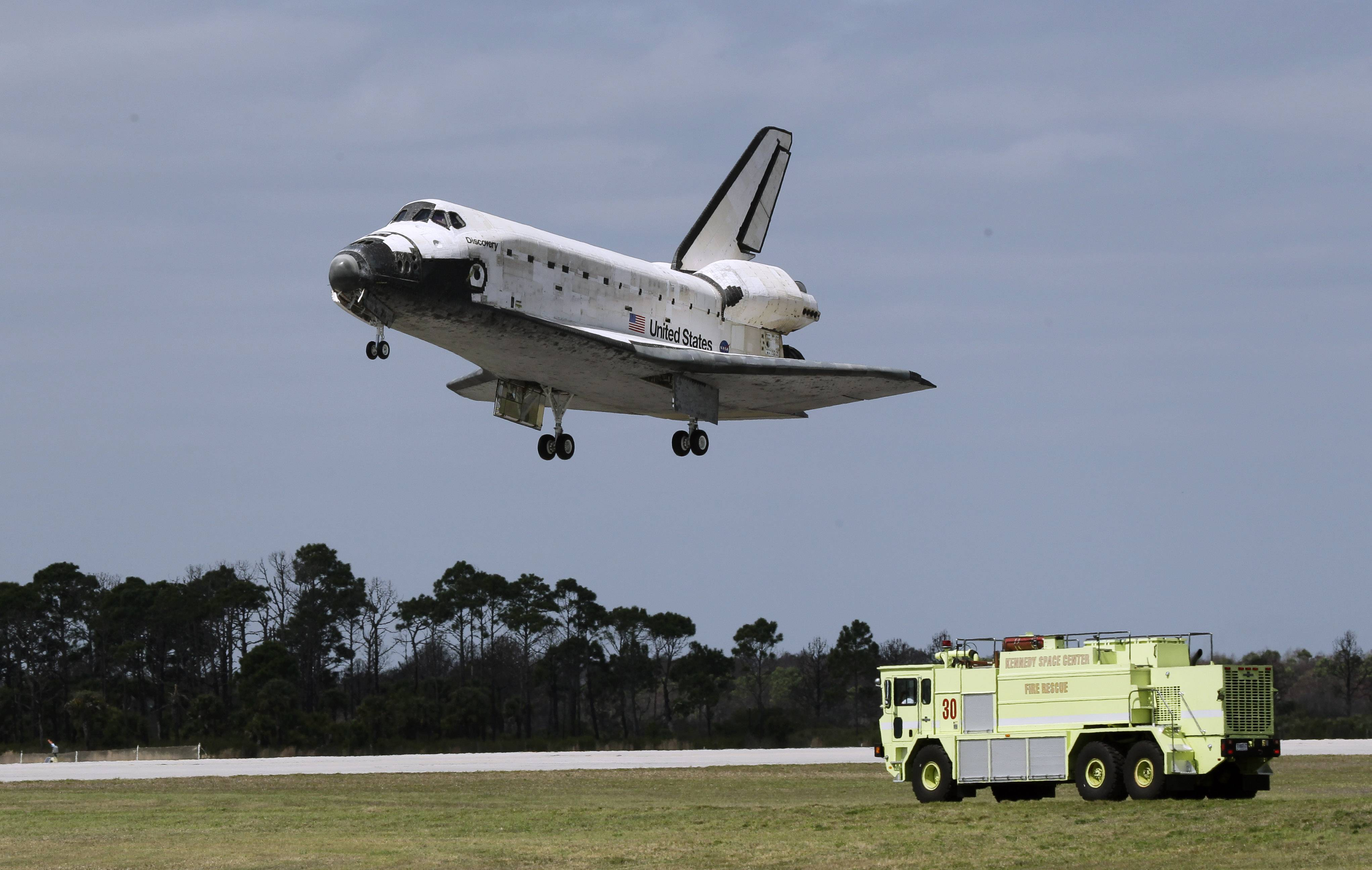 An emergency vehicle stands by near the runway as space shuttle Discovery lands at the Kennedy Space Center in Cape Canaveral, Fla.