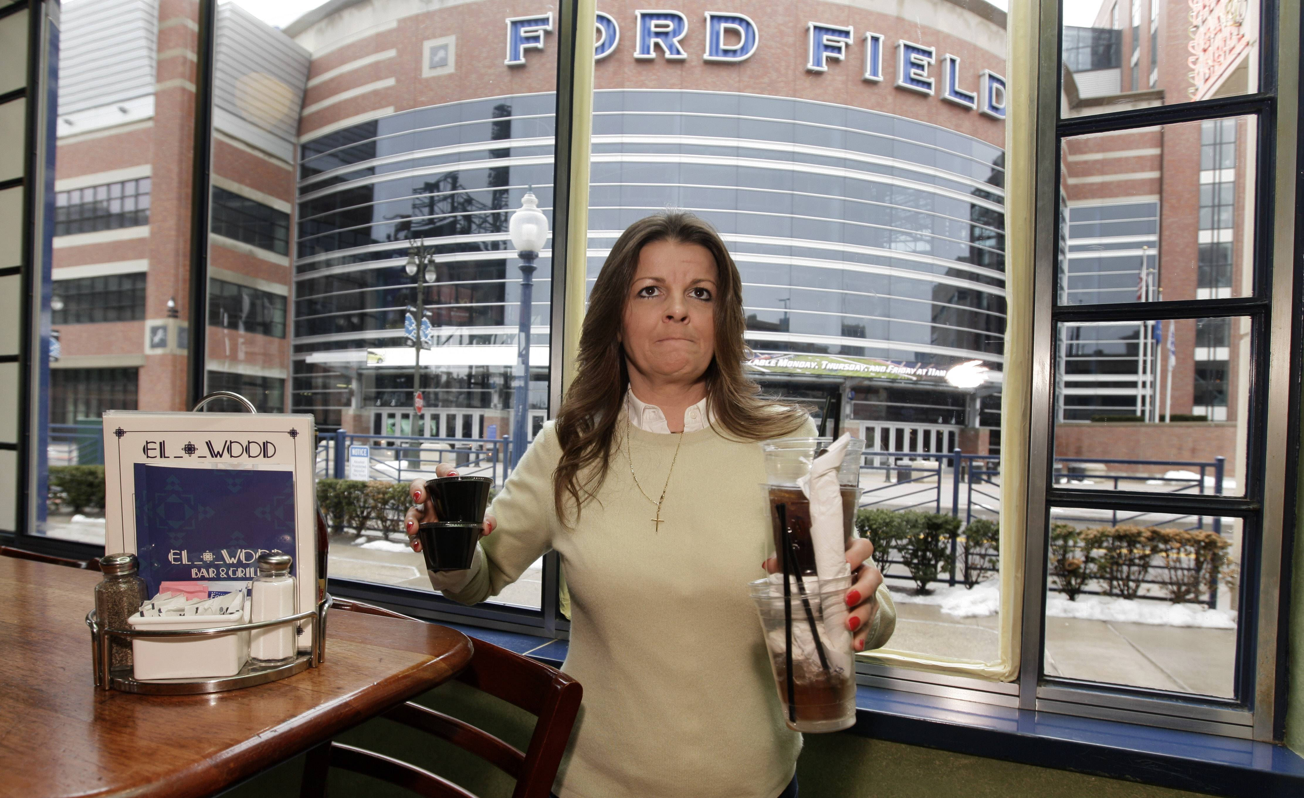 Elwood Bar & Grill manager Liz Markle clears a table with a view of Ford Field in Detroit, home to NFL football's Detroit Lions.