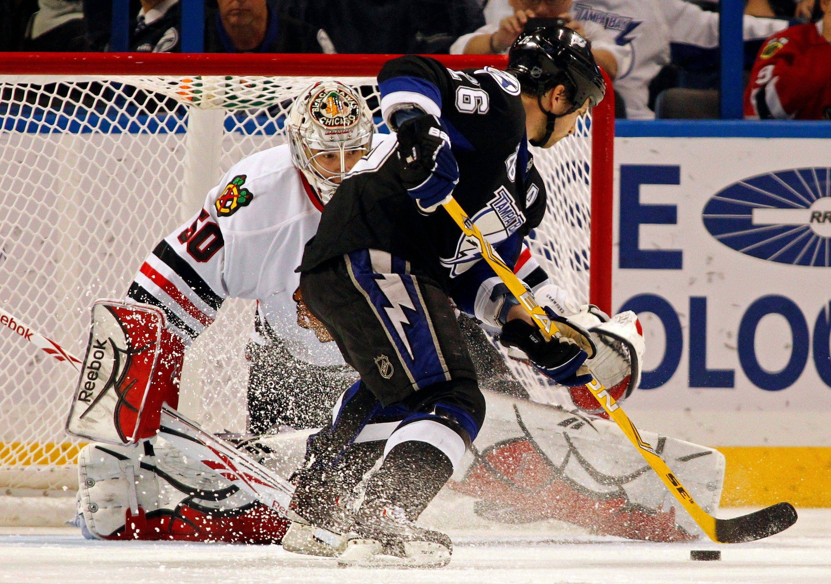 Tampa Bay Lightning's Martin St. Louis scores the game winning goal in a shootout past Chicago Blackhawks goalie Corey Crawford during Wednesday game in Tampa, Fla.