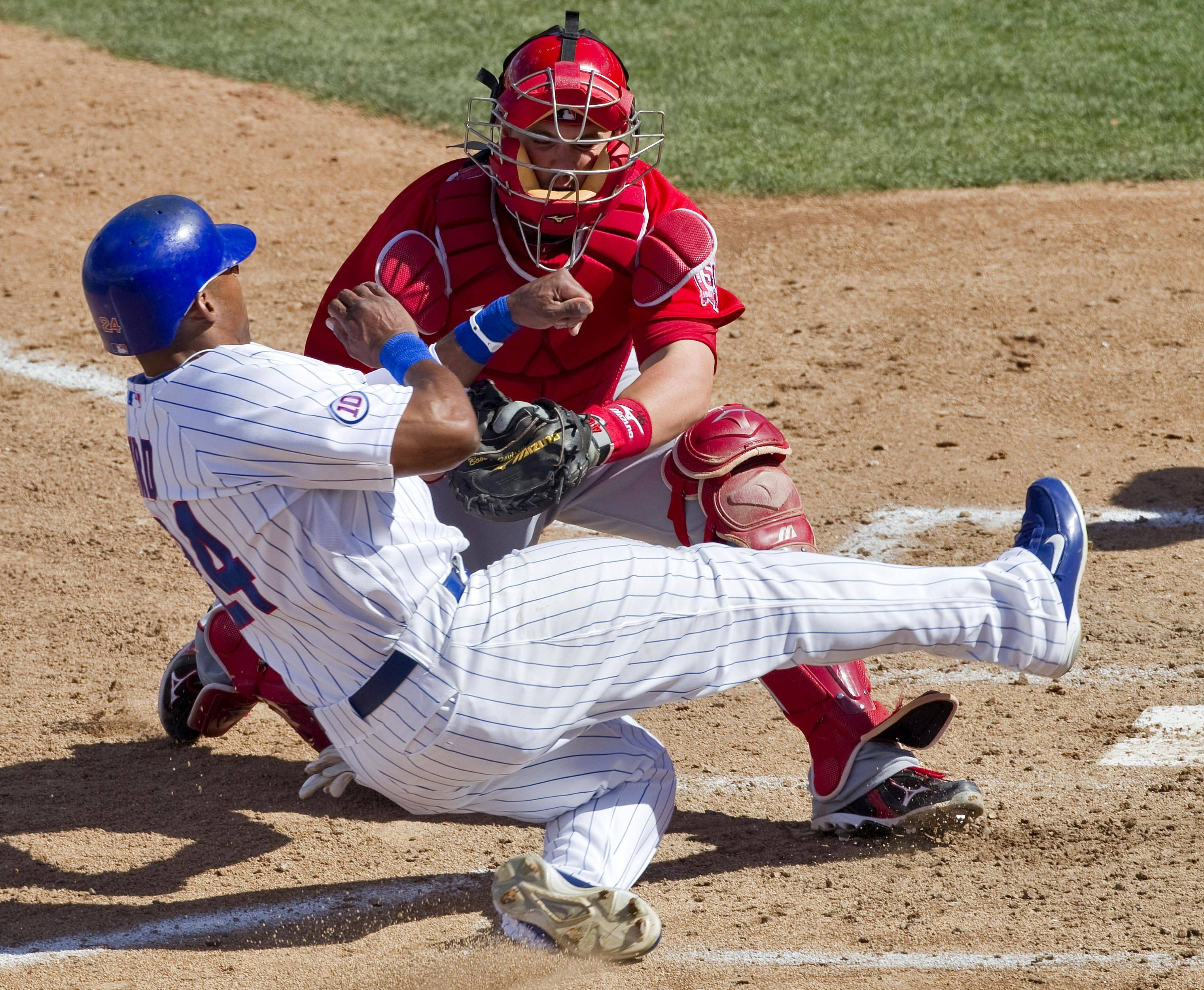 Angels catcher Bobby Wilson tags out Marlon Byrd of the Cubs during their spring training game at HoHo Kam Park on Monday in Mesa, Ariz. Byrd has two years remaining on a three-year deal he signed last season.