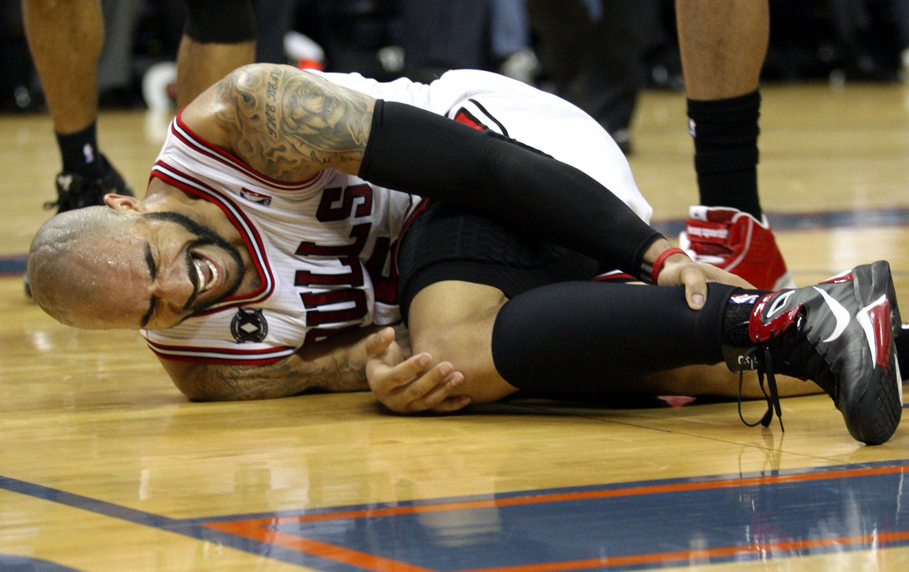 Chicago Bulls forward Carlos Boozer writhes in pain after getting injured during the second half of thel game against the Bobcats in Charlotte, N.C.