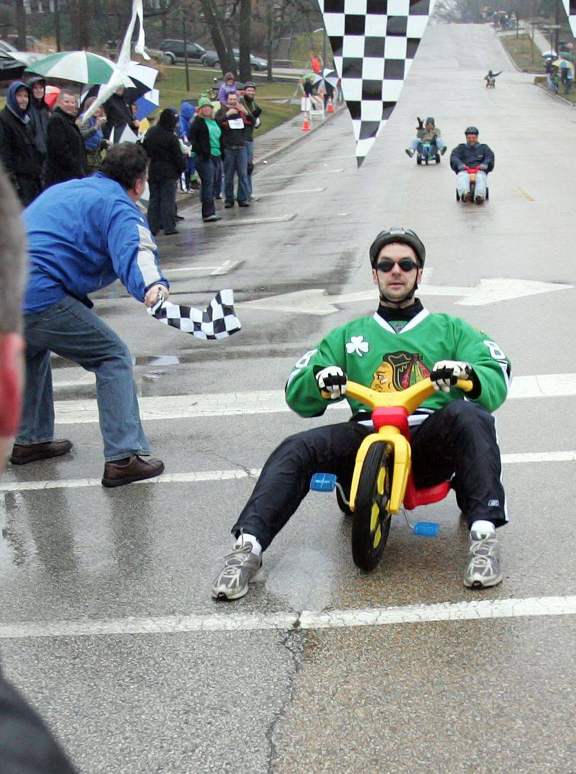 Dave Pape of West Dundee crosses the finish line to take first during the finals of the Big Wheel races in West Dundee at last year's St. Patrick's Day parade.