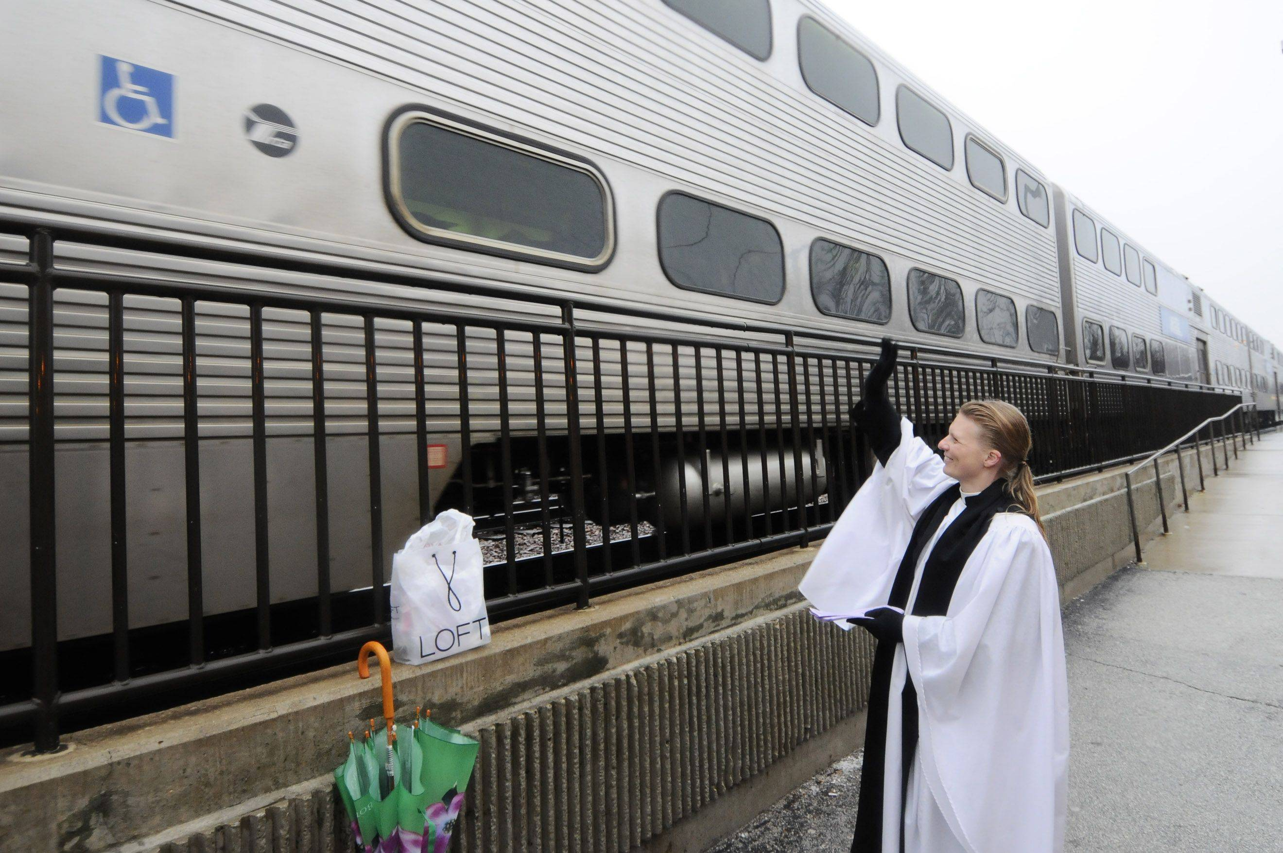Rev. Emily Mellott waves to commuters on the train as it pulls out of the Lombard station Wednesday. She was on hand to distribute ashes to commuters on Ash Wednesday.
