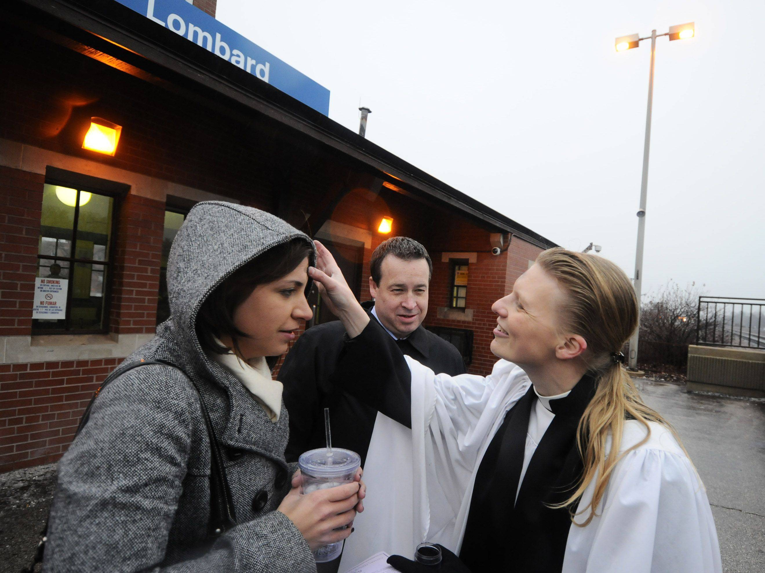 Kristin Krol, left, and Tom O'Hara, center, both from Lombard, receive ashes from Rev. Emily Mellot, right, before getting on their train Wednesday. A program offered by Calvary Episcopal Church in Lombard called Ashes To Go, brought ashes for Ash Wednesday to commuters Wednesday at Lombard's commuter station. Reverend Emily Mellott, pastor of Calvary Episcopal was on hand in vestments along with several other assistants to read a brief prayer and place ashes on the foreheads of any commuter who wished, and had time before dashing off to the trains.