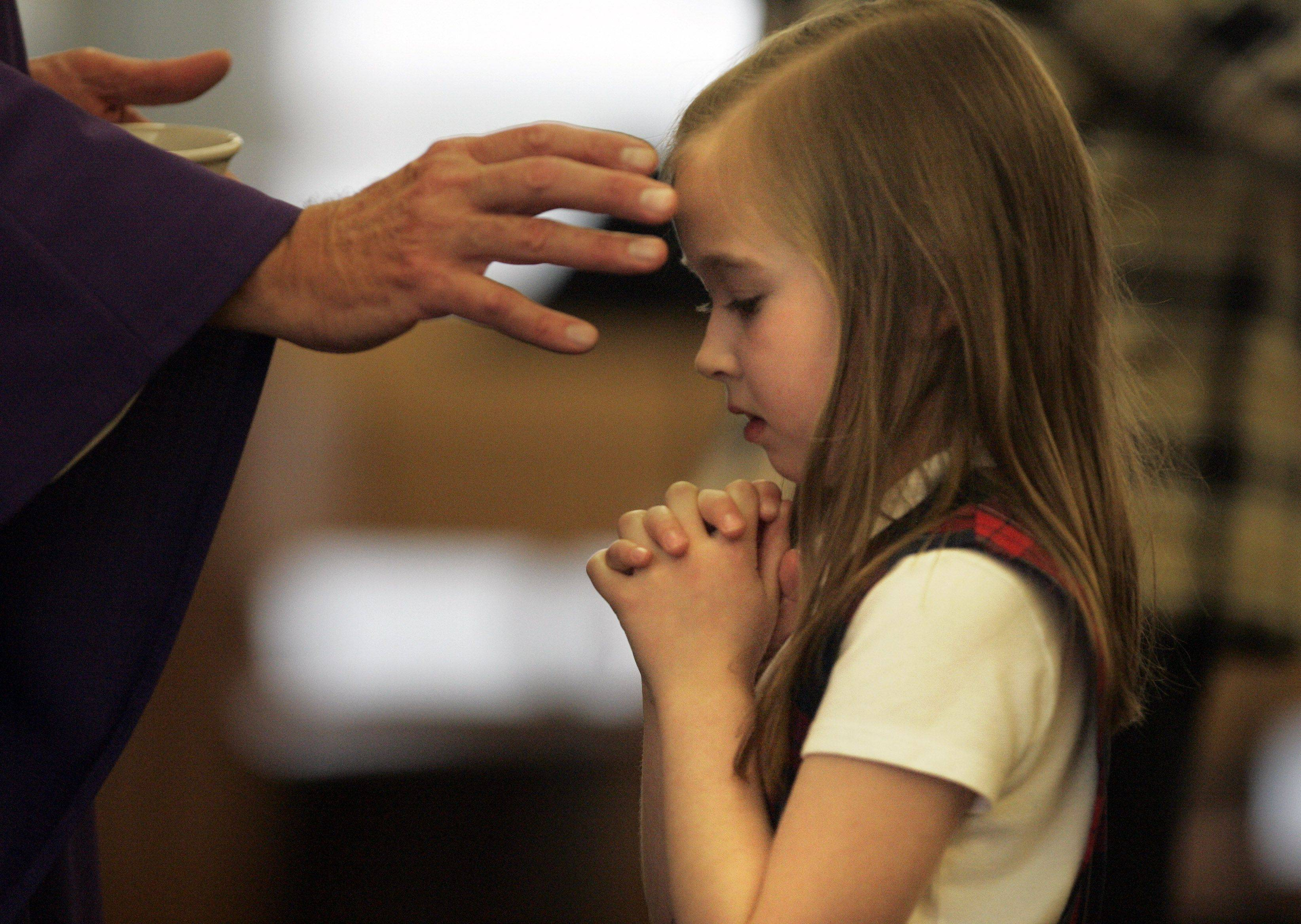 Father Wirth distributes ashes to first-grade student Isabel Galla during Ash Wednesday mass at St. Thomas More Catholic Church in Elgin Wednesday.