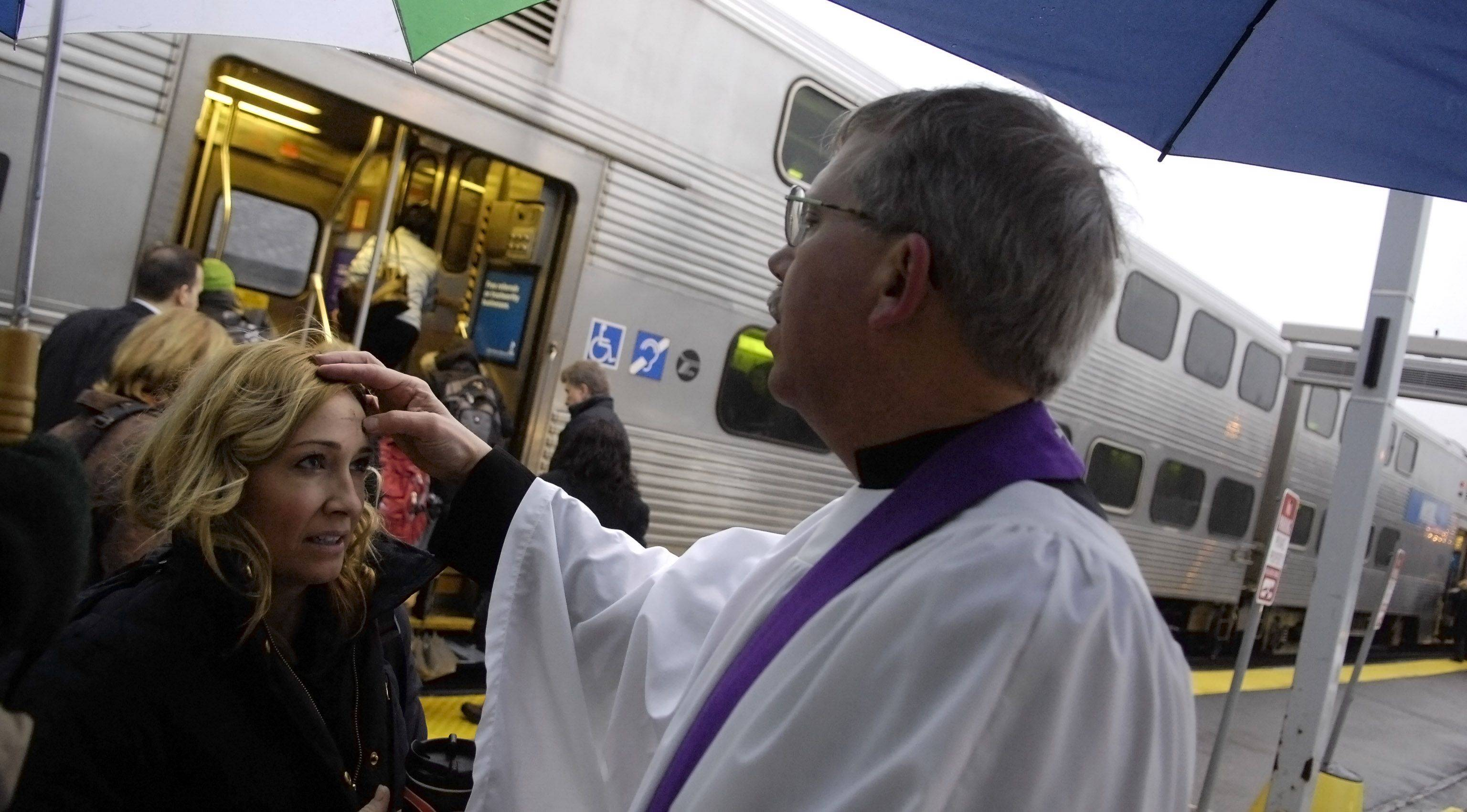 Rev. Nesbit administers ashes to commuter Joy Saris of Geneva at the Geneva Metra station on Ash Wednesday.