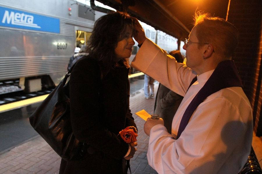 The Rev. M.E. Eccles, associate rector with St. Simon's Episcopal Church in Arlington Heights offers the imposition of ashes to Rita Sliwa of Arlington Heights just before she got on the train headed to Chicago at the downtown Arlington Heights Metra station on Wednesday, March 9th.