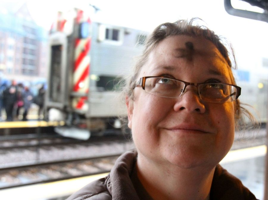 Mary Kurbat of Wheeling looks up after Rev. M.E. Eccles, associate rector with St. Simon's Episcopal Church in Arlington Heights presented the imposition of ashes to her and other morning commuters at the downtown Arlington Heights Metra station on Wednesday, March 9th.