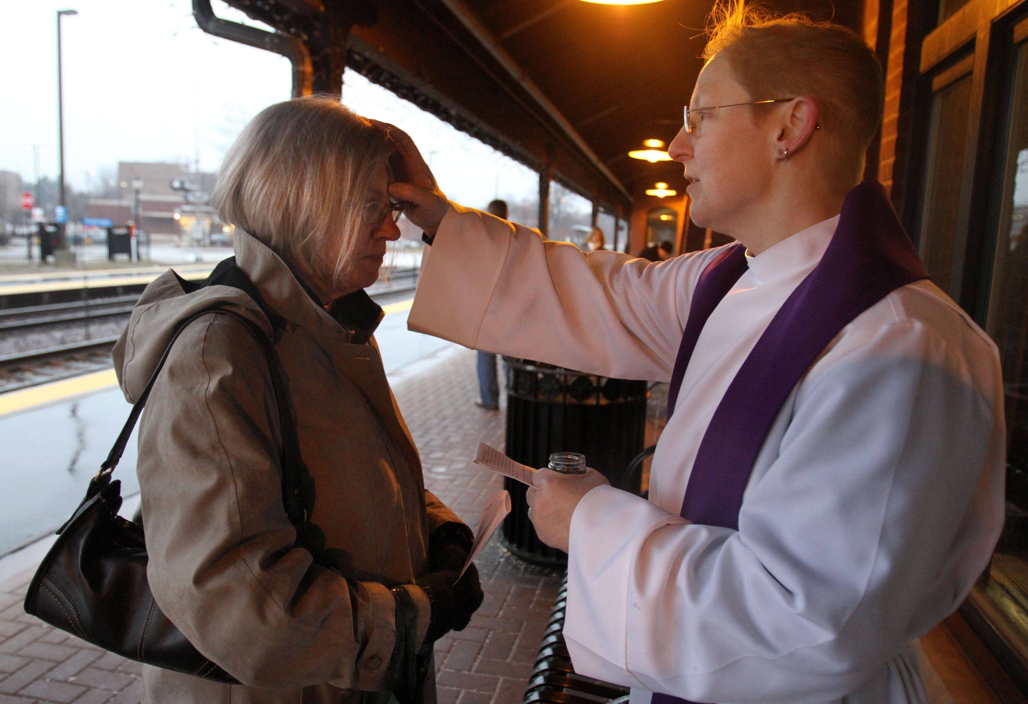 The Rev. M.E. Eccles, associate rector with St. Simon's Episcopal Church in Arlington Heights offers the imposition of ashes to morning commuter Mary Lou Gleason of Arlington Heights at the downtown Arlington Heights Metra station on Wednesday, March 9th.