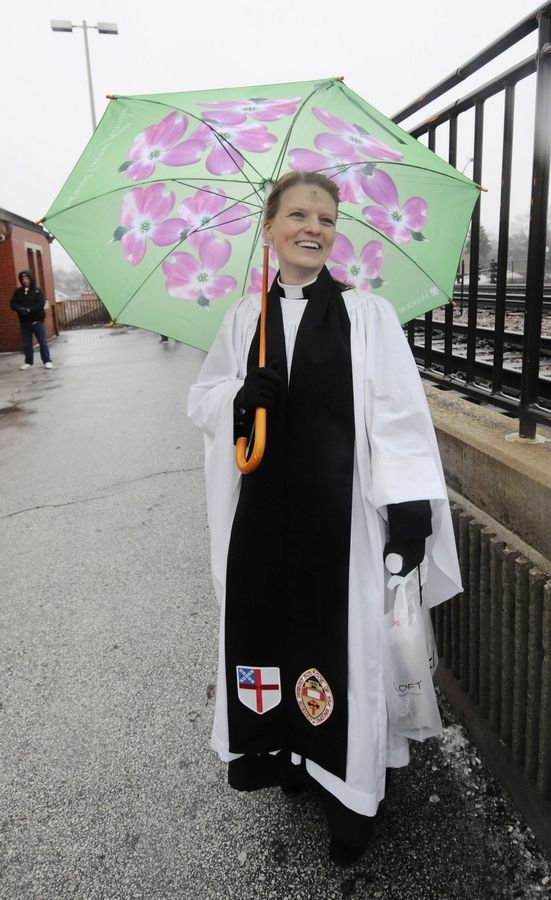 "Rev. Emily Mellott, pastor of Calvary Episcopal Church in Lombard watches a train Wednesday at the Lombard train Metra station in vestments, complete with umbrella and supplies in a shopping bag. ""I'm all layered up underneath,"" she said."