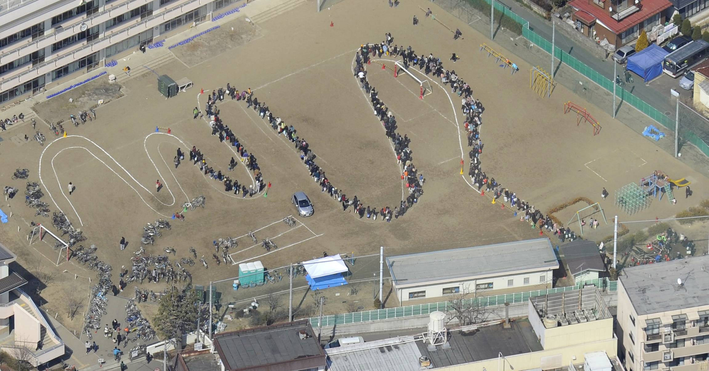 A long line of residents seeking water supply is formed on the playground of a school in Sendai, northeastern Japan, on Sunday March 13, 2011, two days after a powerful earthquake and tsunami hit the the country's northeastern coast.
