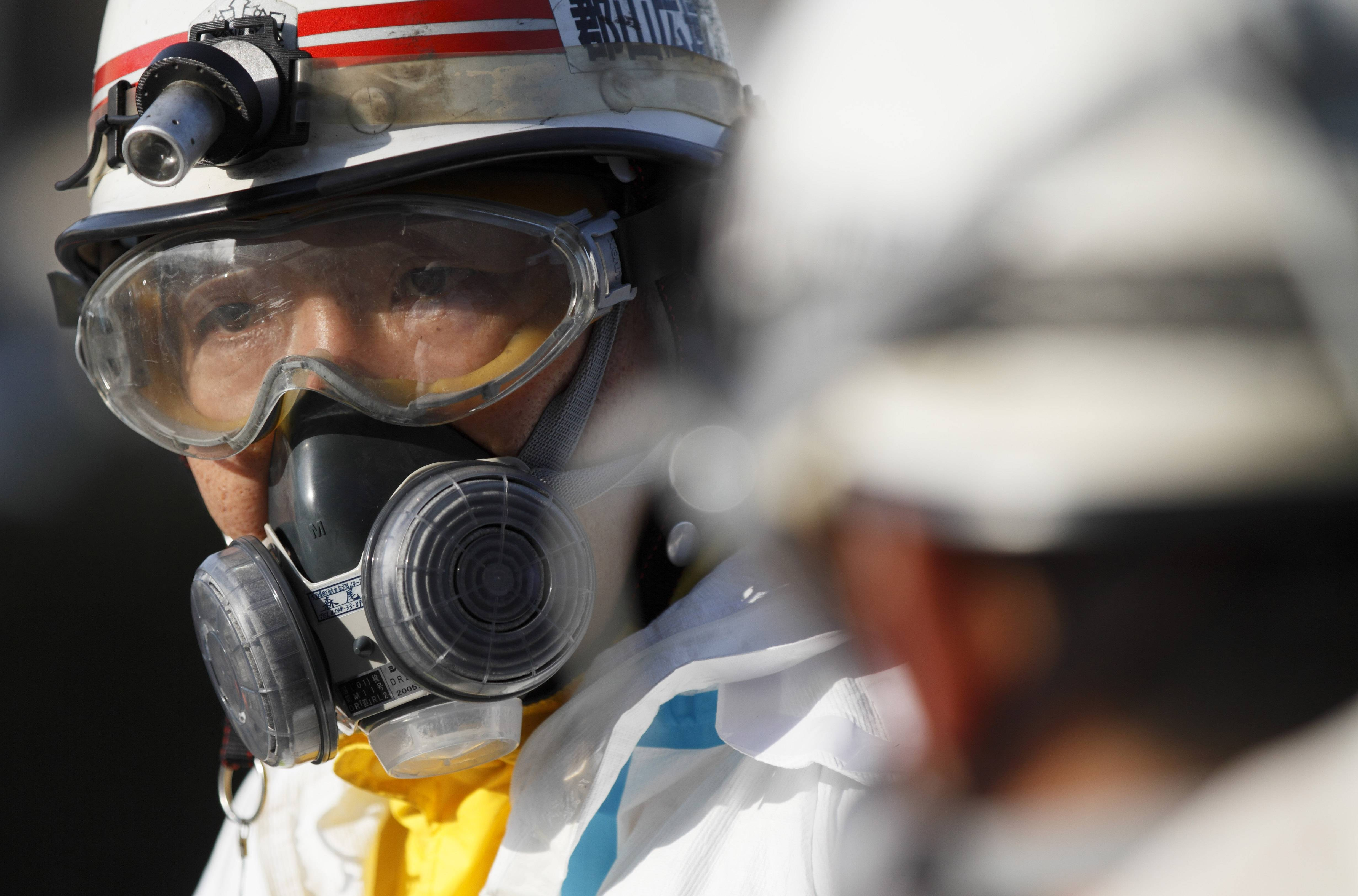 An official wears protective clothing while waiting to scan people for radiation an emergency center on Sunday, March 13, 2011, in Koriyama, northeastern Japan, two days after a giant quake and tsunami struck the country's northeastern coast.