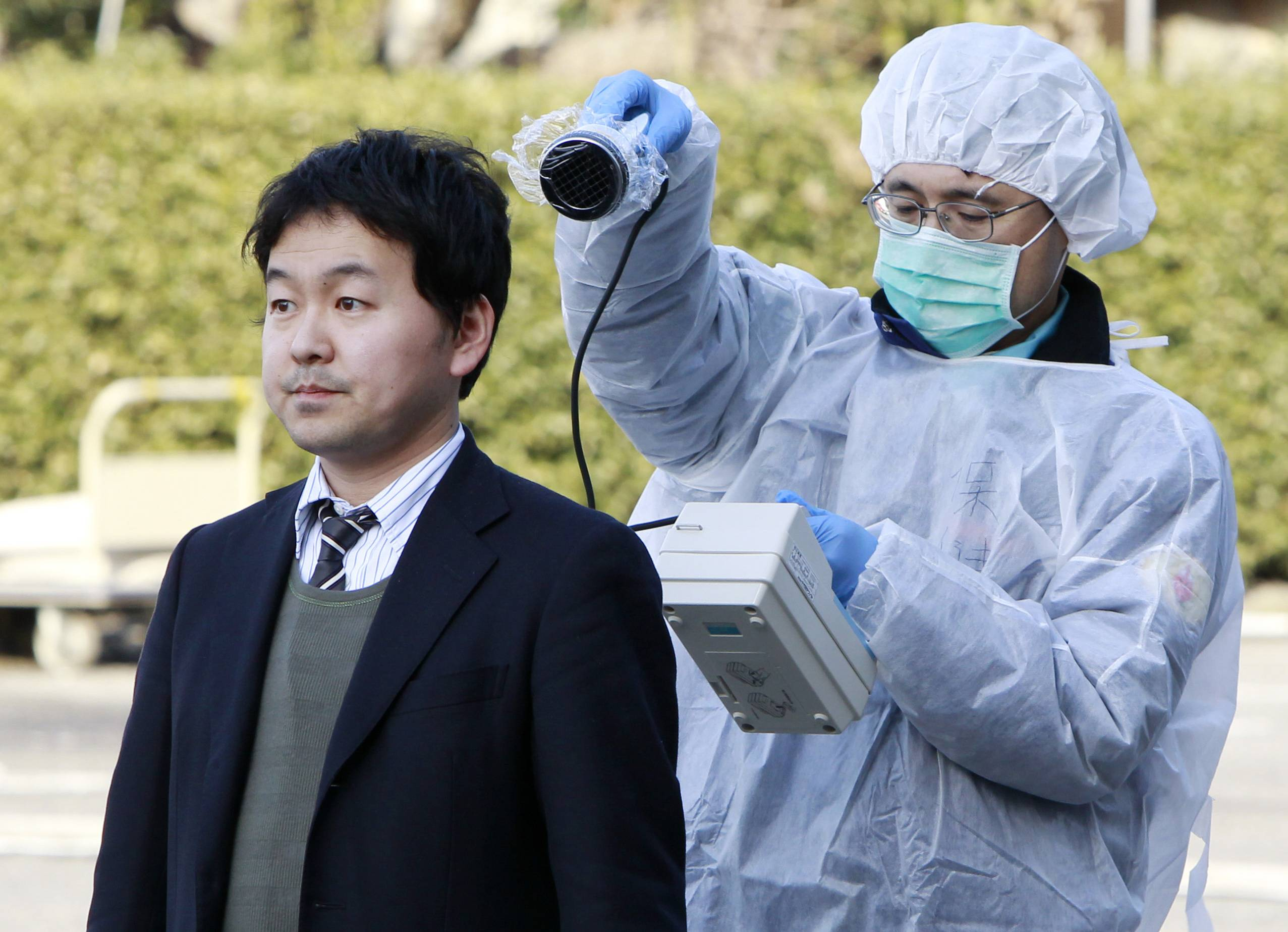 A man stands to be checked for levels of radiation in Koriyama, northeastern Japan, Sunday, March 13, 2011, two days after a giant quake and tsunami struck the country's northeastern coast.