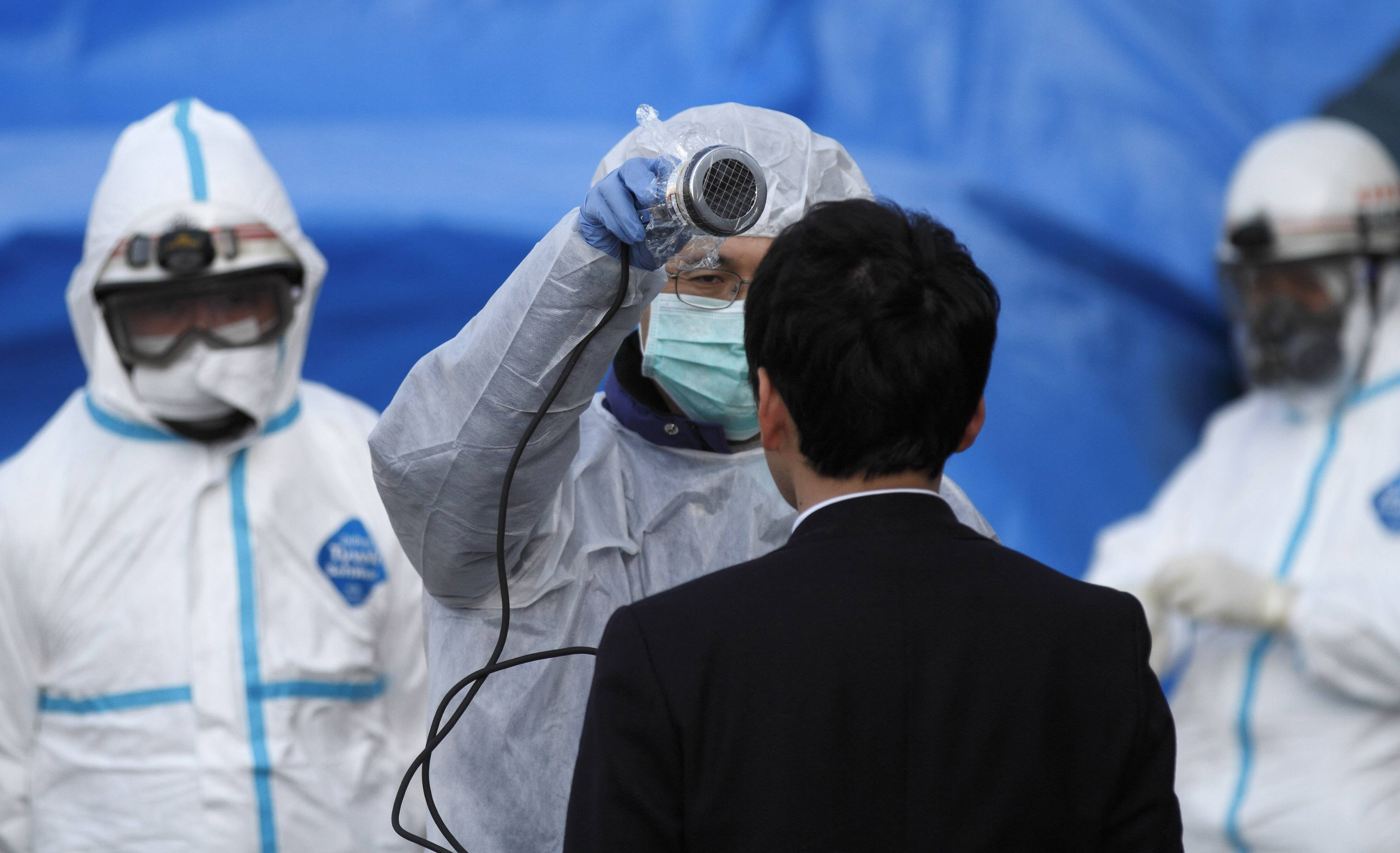 An official scans a man for radiation at an emergency center Sunday, March 13, 2011, in Koriyama, northeastern Japan, two days after a giant quake and tsunami struck the country's northeastern coast.