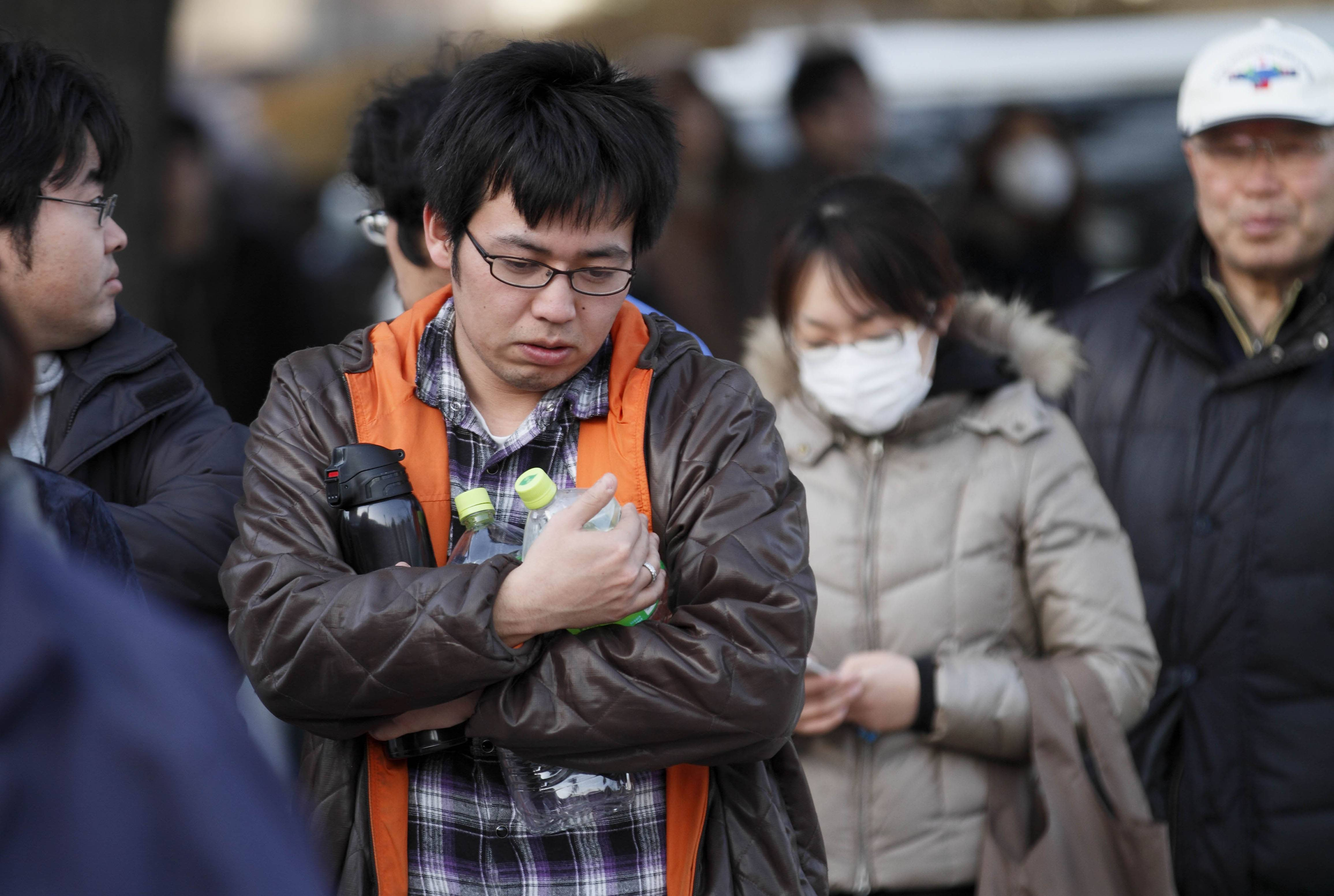 A man holds empty bottles as he waits for water an emergency center on Sunday, March 13, 2011, in Koriyama, northeastern Japan, two days after a giant quake and tsunami struck the country's northeastern coast.
