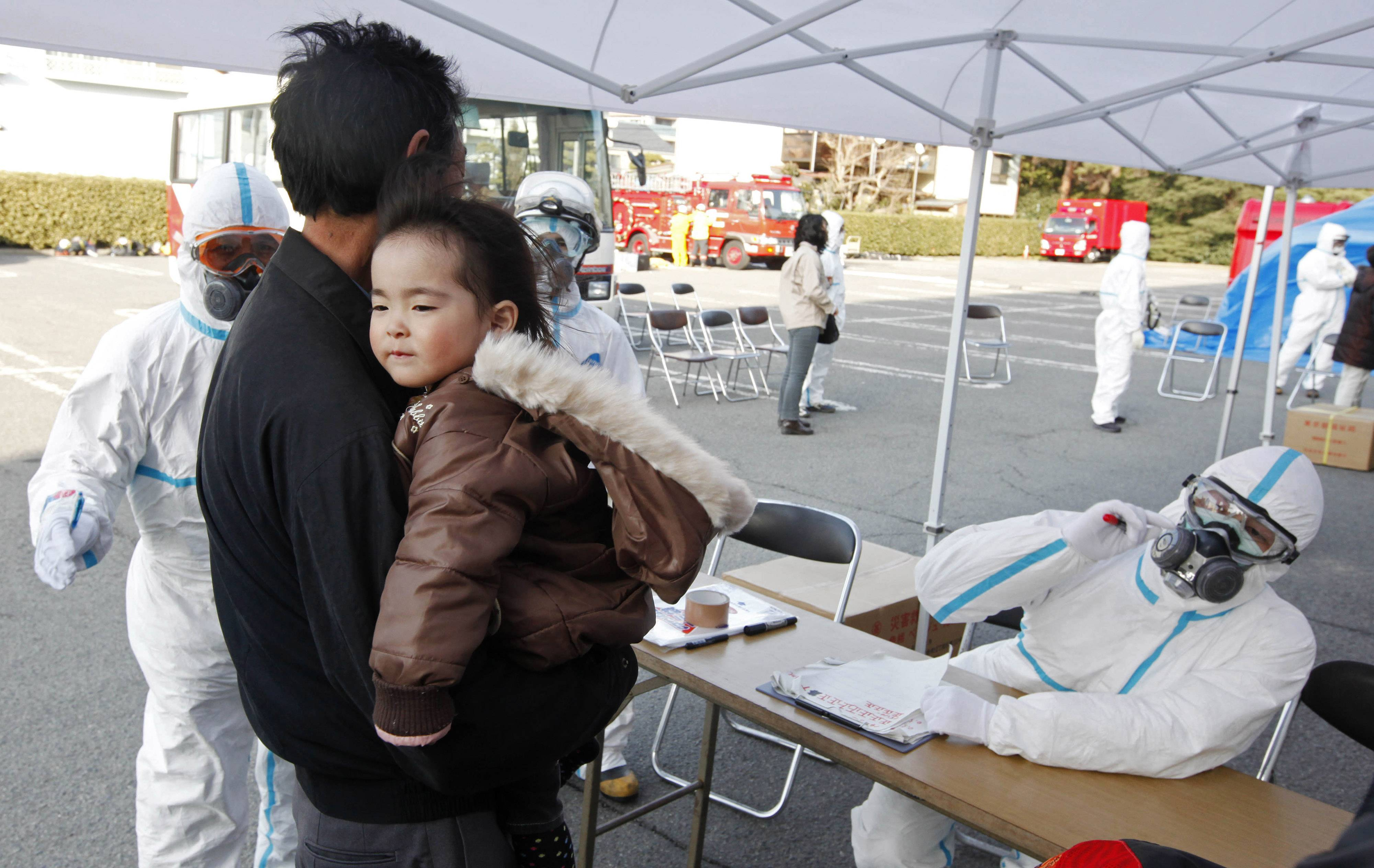 A man holds his baby as they are prepared to be scanned for levels of radiation in Koriyama, Fukushima Prefecture, Japan, Sunday, March 13, 2011. Friday's quake and tsunami damaged two nuclear reactors at a power plant in the prefecture, and at least one of them appeared to be going through a partial meltdown, raising fears of a radiation leak.